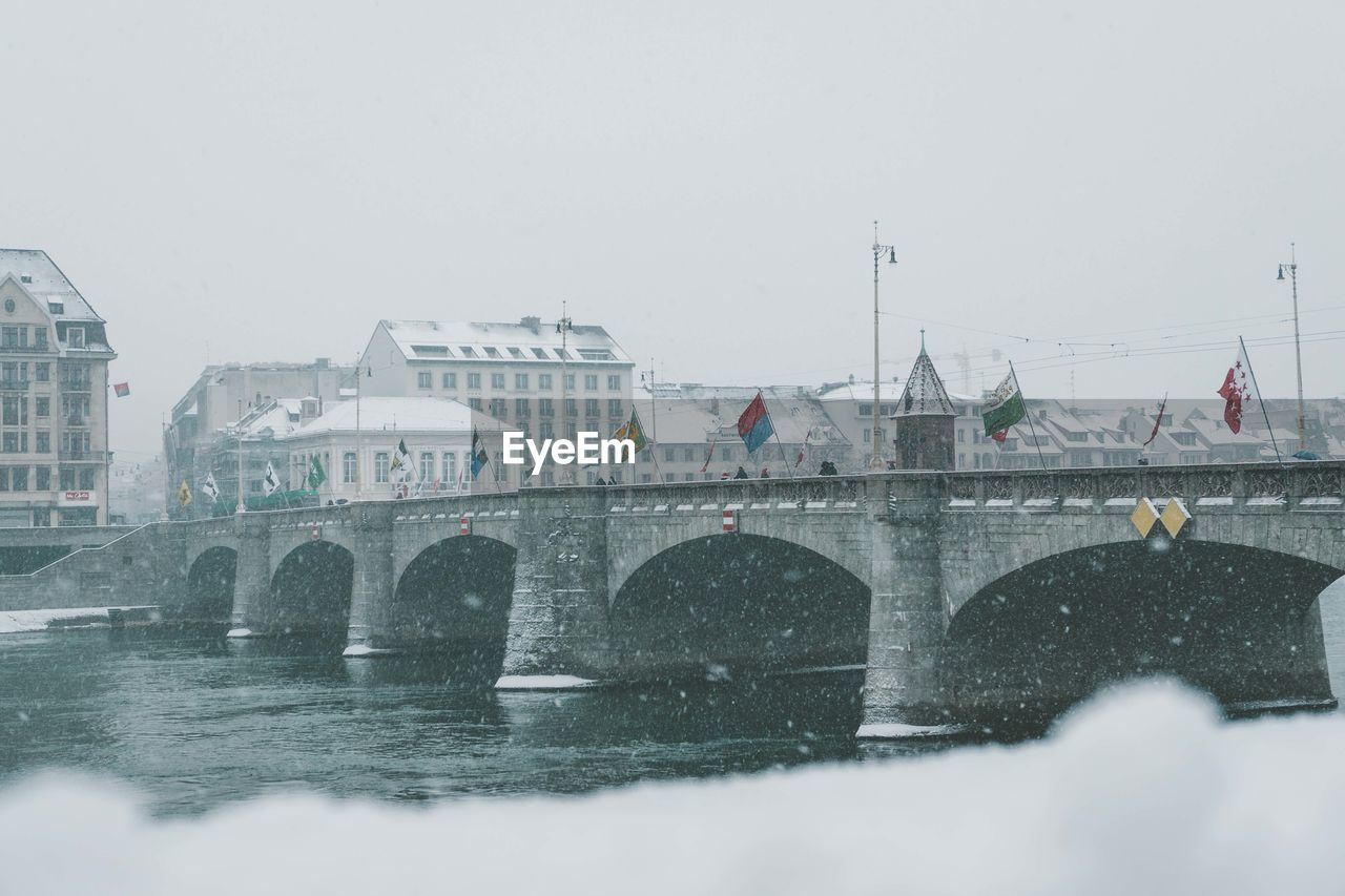 architecture, built structure, building exterior, cold temperature, winter, bridge, water, sky, nature, transportation, bridge - man made structure, snow, connection, city, river, day, clear sky, waterfront, snowing, no people, outdoors, arch bridge
