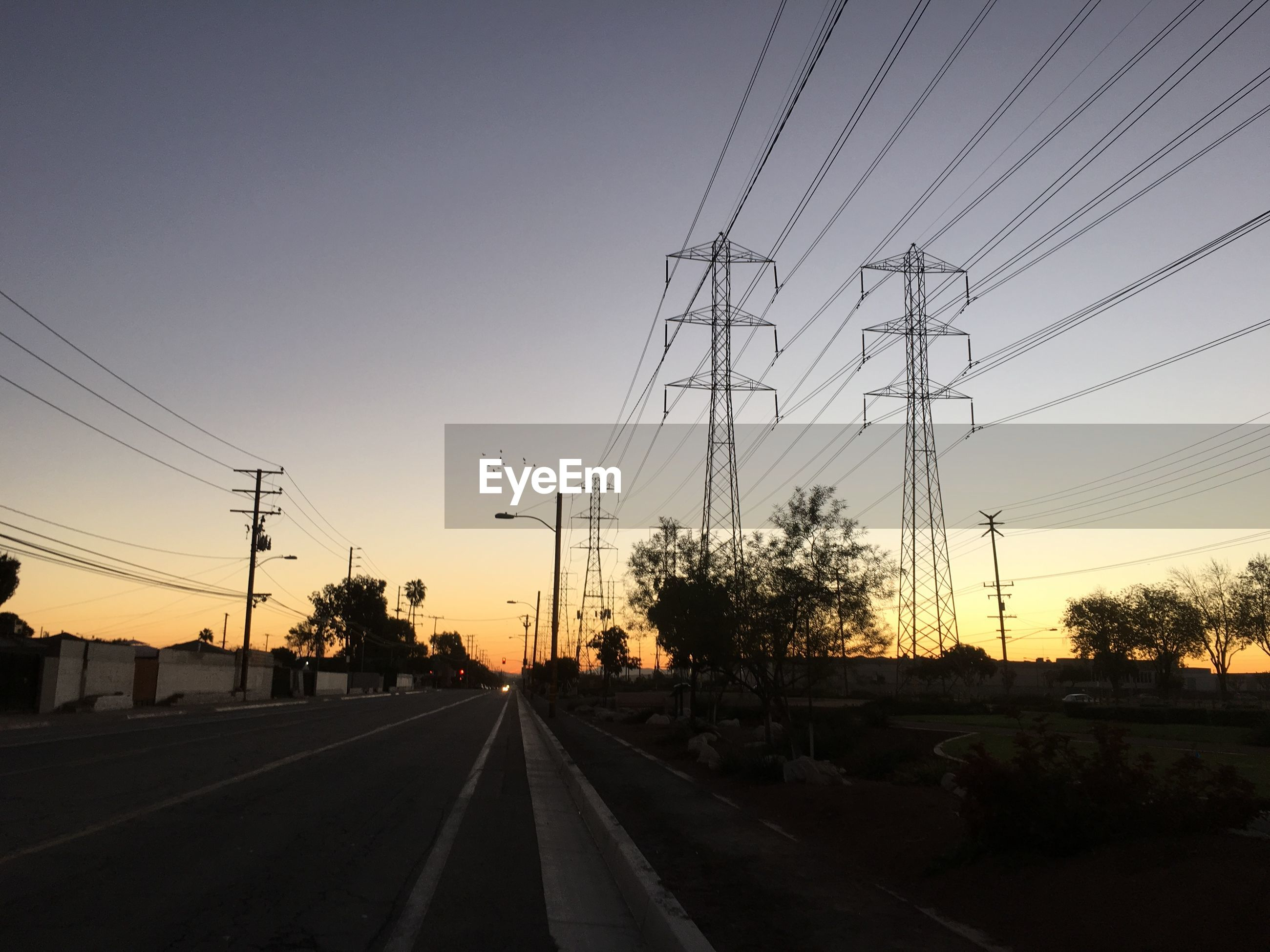 Low angle view of electricity pylons by road against sky during sunset