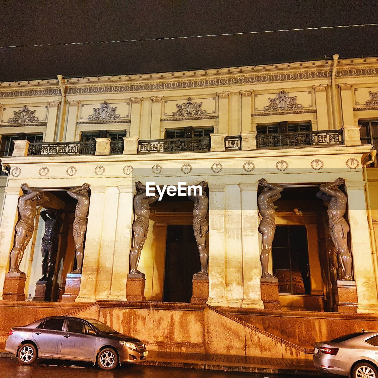 architecture, built structure, building exterior, mode of transportation, the past, history, transportation, city, car, motor vehicle, no people, land vehicle, travel, night, window, building, communication, low angle view, architectural column, outdoors, luxury