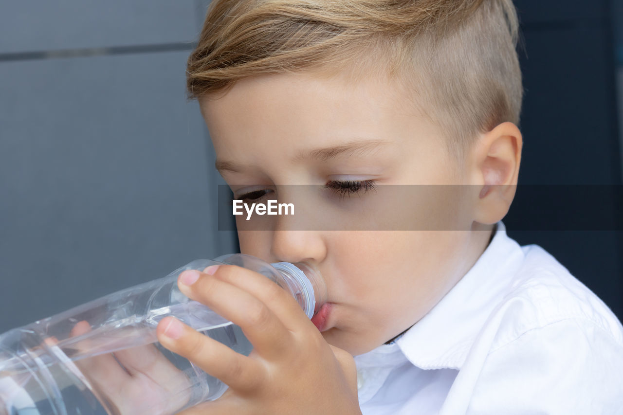 PORTRAIT OF A BOY DRINKING WATER FROM GLASS