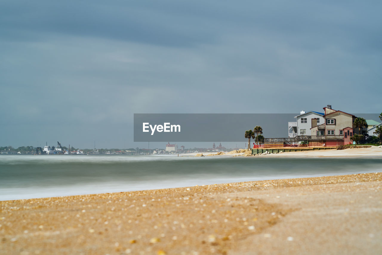 water, beach, land, sea, built structure, architecture, building exterior, cloud - sky, sky, sand, nature, beauty in nature, scenics - nature, day, building, motion, wave, outdoors, incidental people