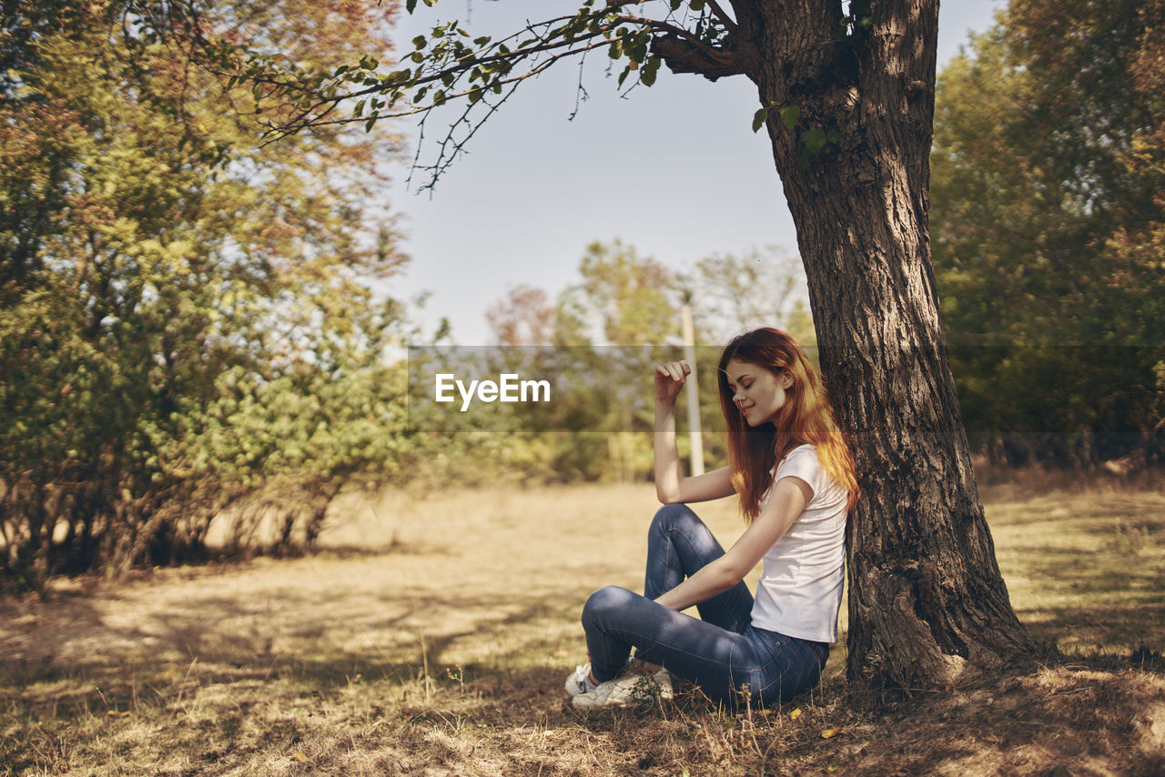 PORTRAIT OF SMILING YOUNG WOMAN SITTING ON TREE TRUNK AGAINST PLANTS