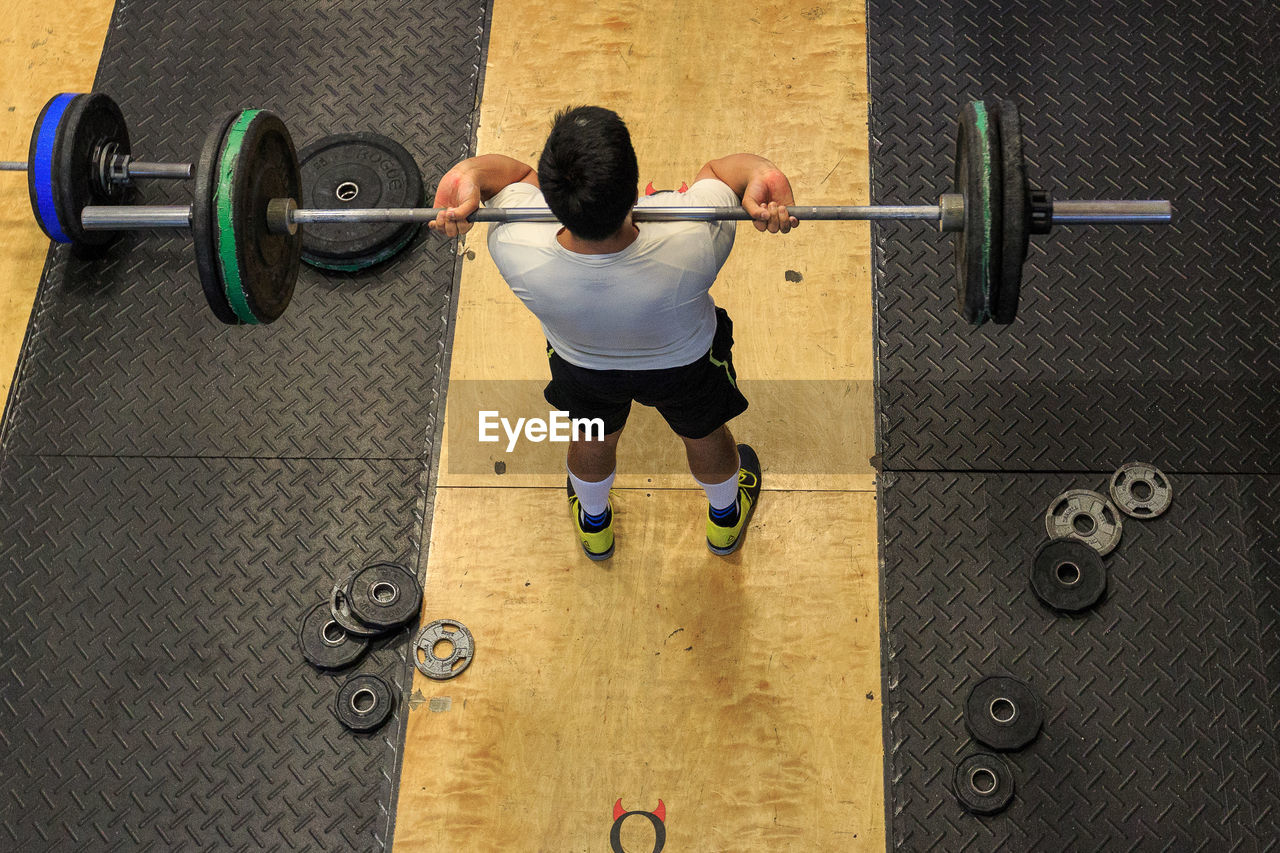 High Angle View Of A Man Exercising With Barbell