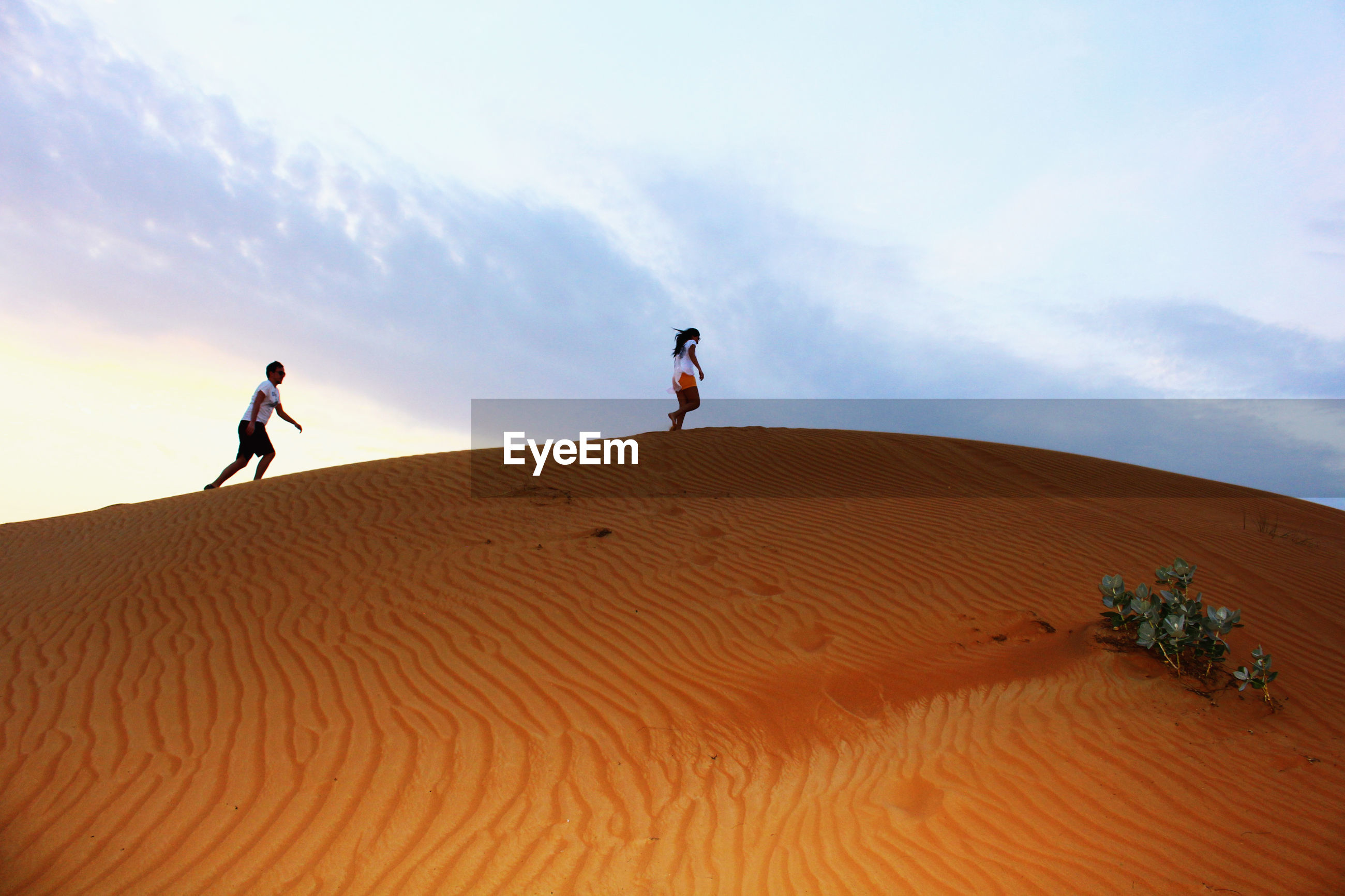 Low angle view of friends walking at desert against cloudy sky
