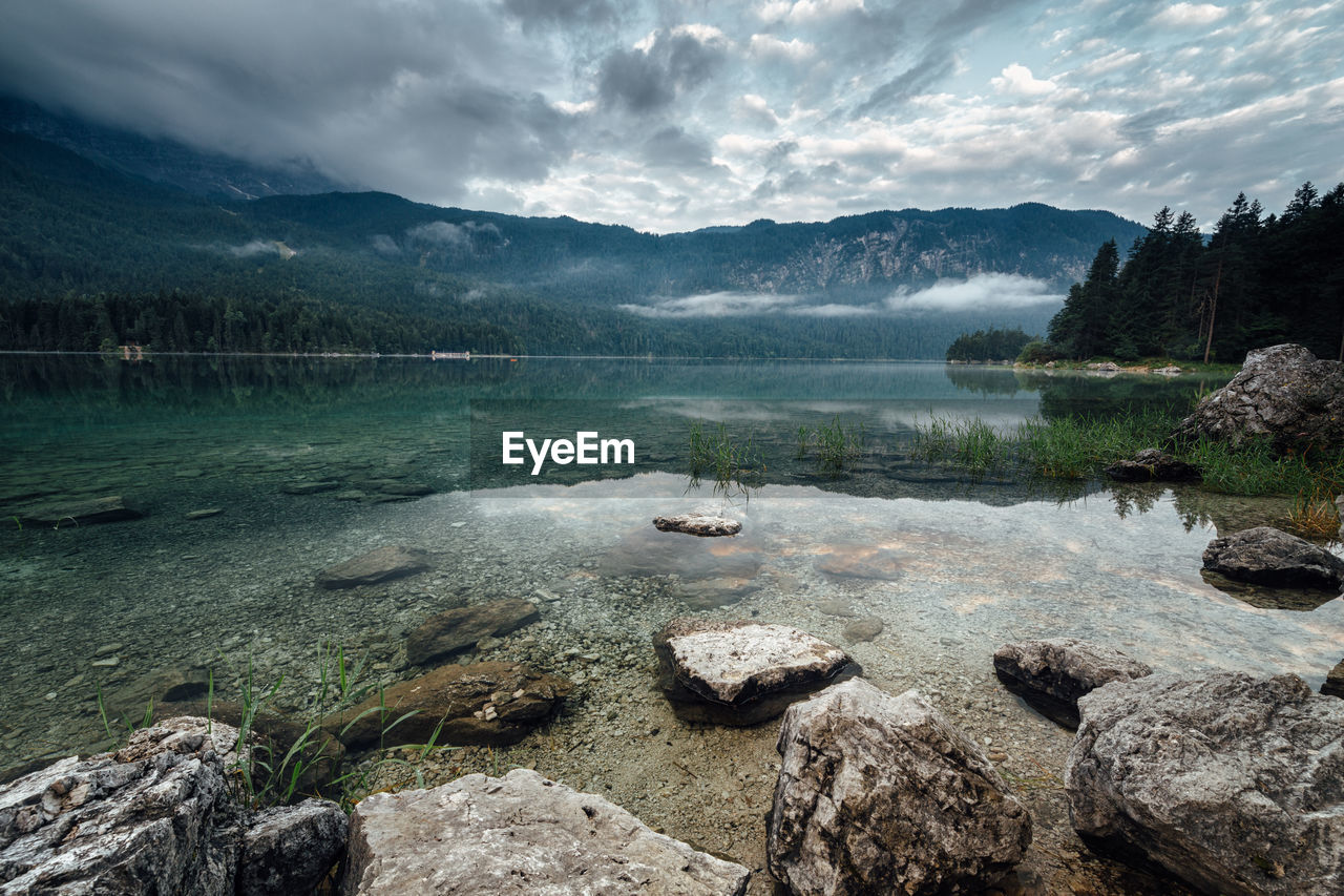 water, mountain, scenics - nature, beauty in nature, cloud - sky, sky, tranquil scene, tranquility, lake, nature, rock, rock - object, day, solid, non-urban scene, no people, mountain range, environment, idyllic, outdoors, hot spring