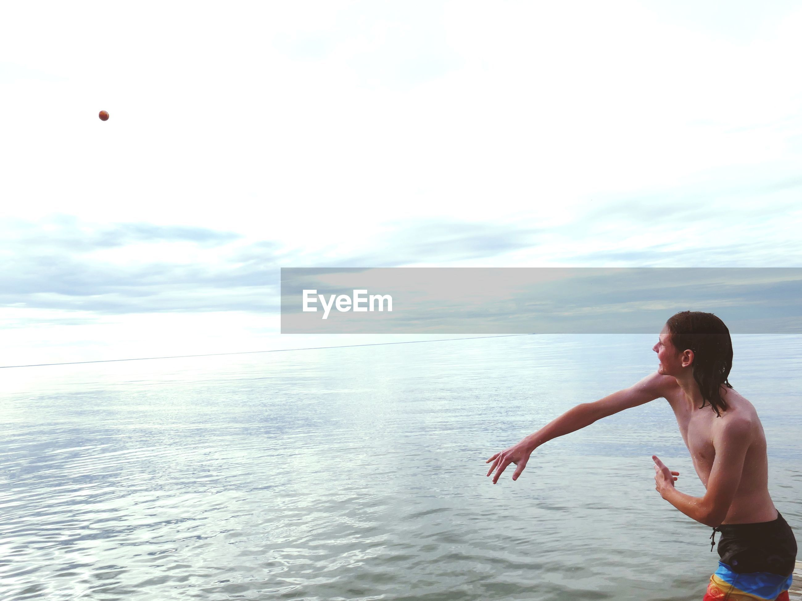 Shirtless boy throwing ball in sea against sky