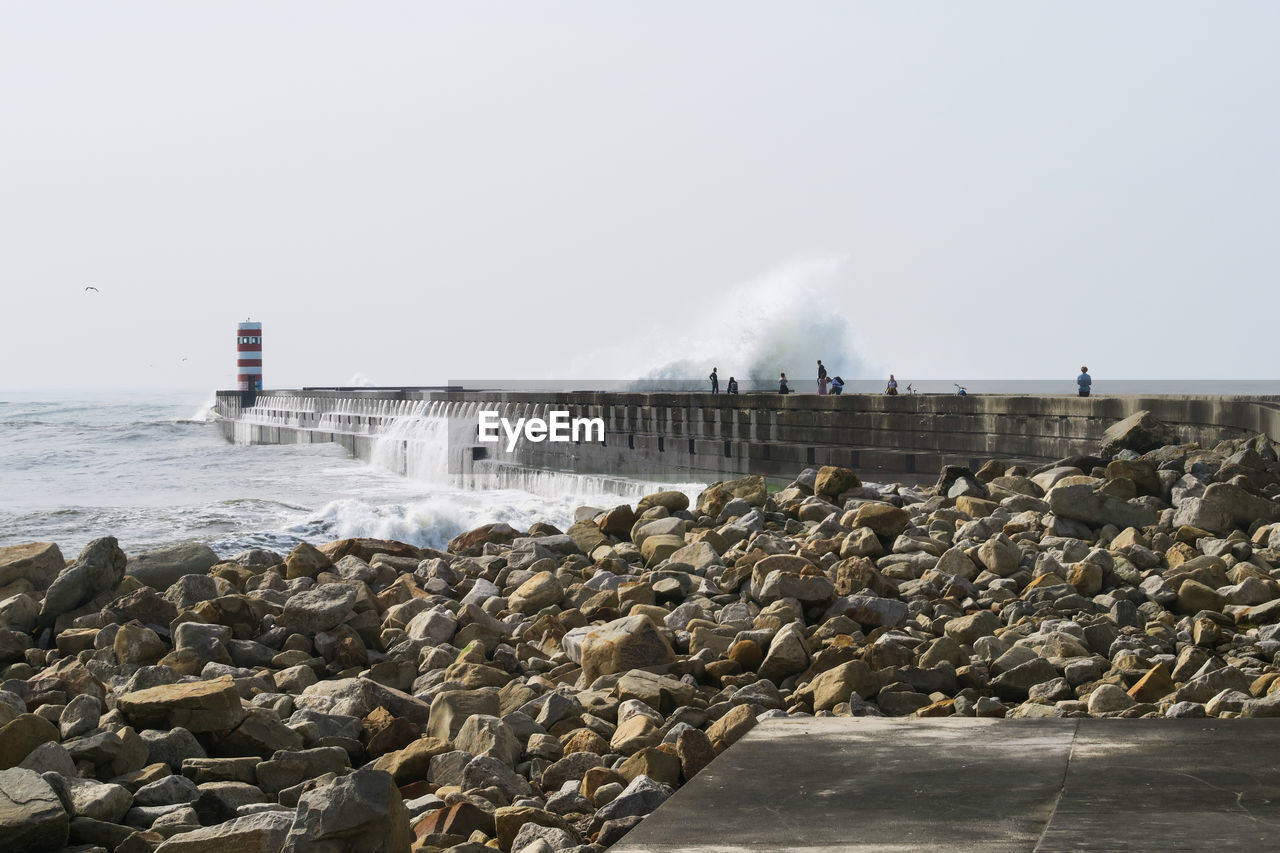 water, sky, rock, solid, rock - object, day, sea, nature, architecture, built structure, clear sky, motion, copy space, building exterior, beach, no people, land, pollution, smoke - physical structure, outdoors, air pollution, groyne