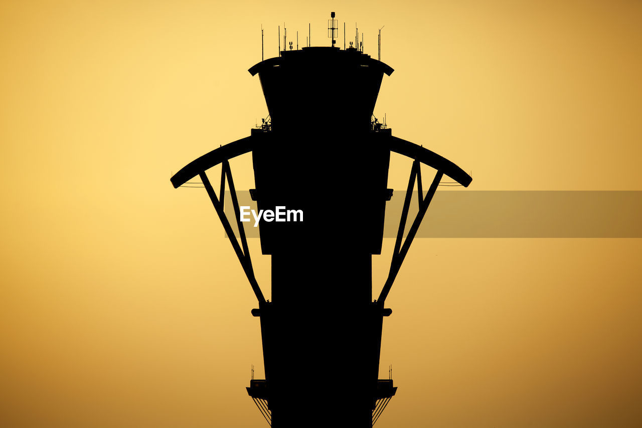 Communications tower against sky during sunset
