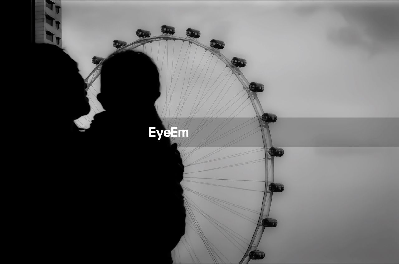 Mother With Baby Looking At Ferris Wheel Against Sky