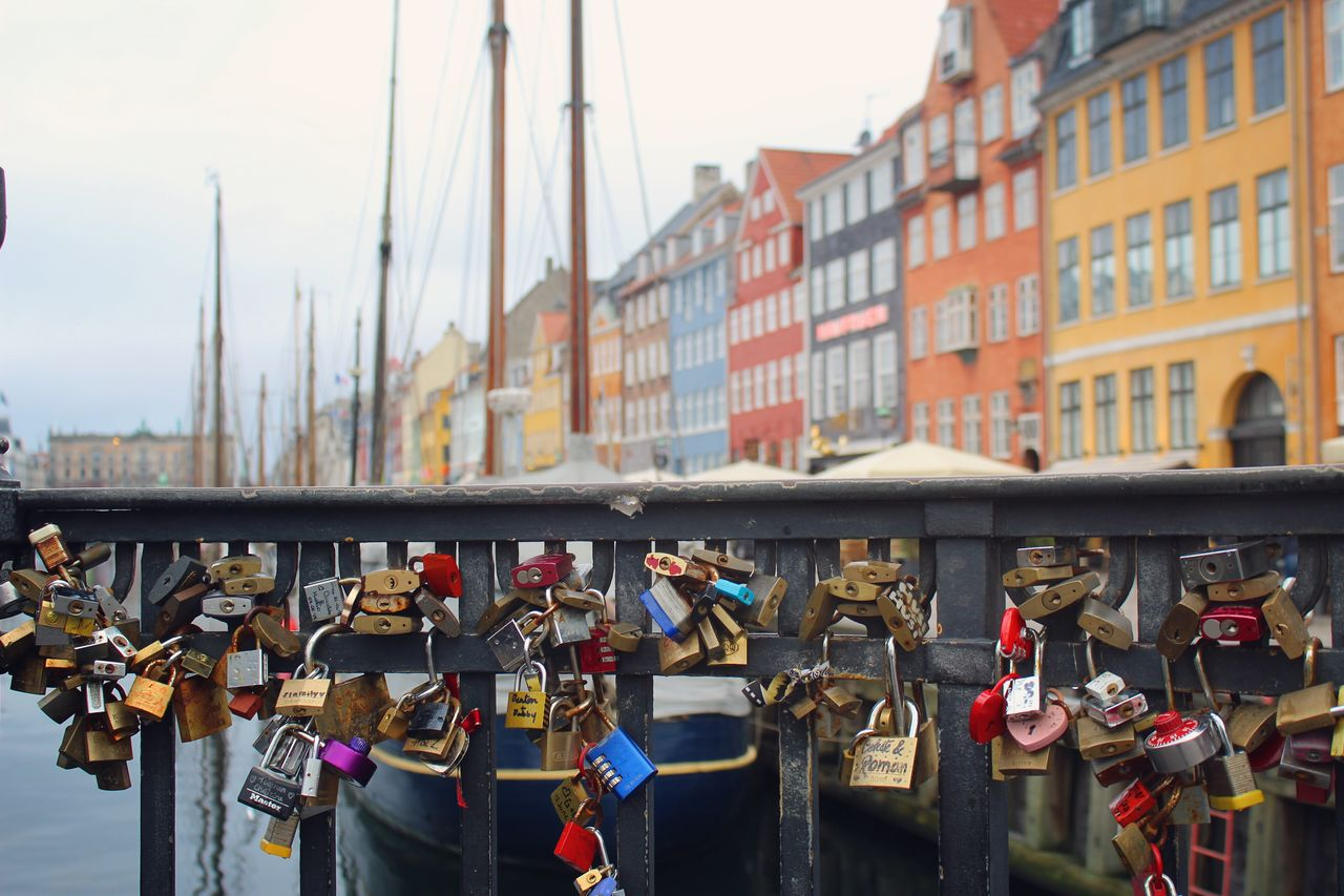 architecture, building exterior, built structure, padlock, lock, protection, day, focus on foreground, city, security, safety, large group of objects, hanging, love lock, connection, outdoors, nature, group of people, positive emotion, emotion