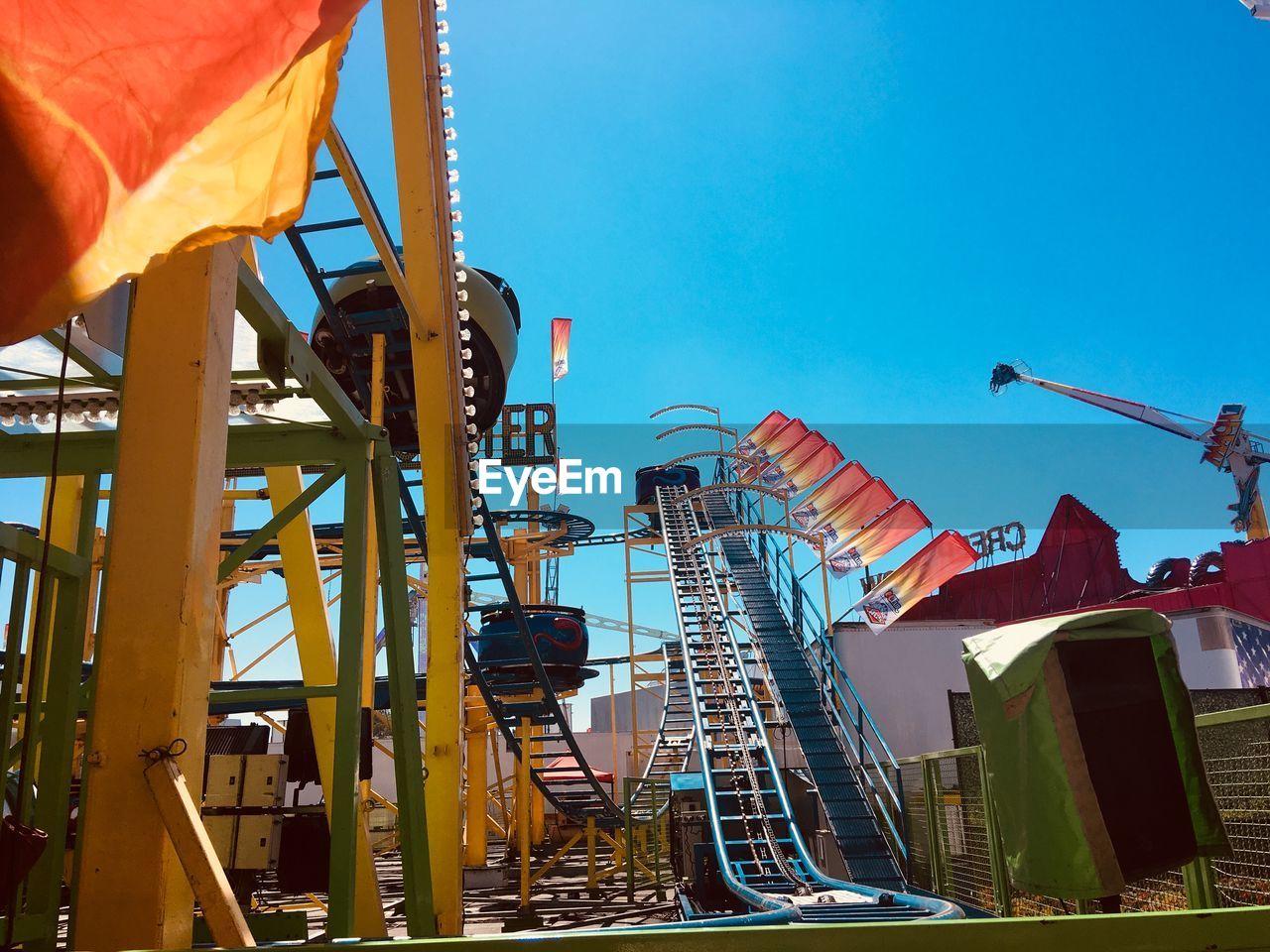 sky, amusement park, architecture, amusement park ride, low angle view, nature, day, clear sky, built structure, arts culture and entertainment, blue, outdoors, no people, rollercoaster, sunlight, metal, leisure activity, building exterior, machinery, enjoyment, excitement, fairground
