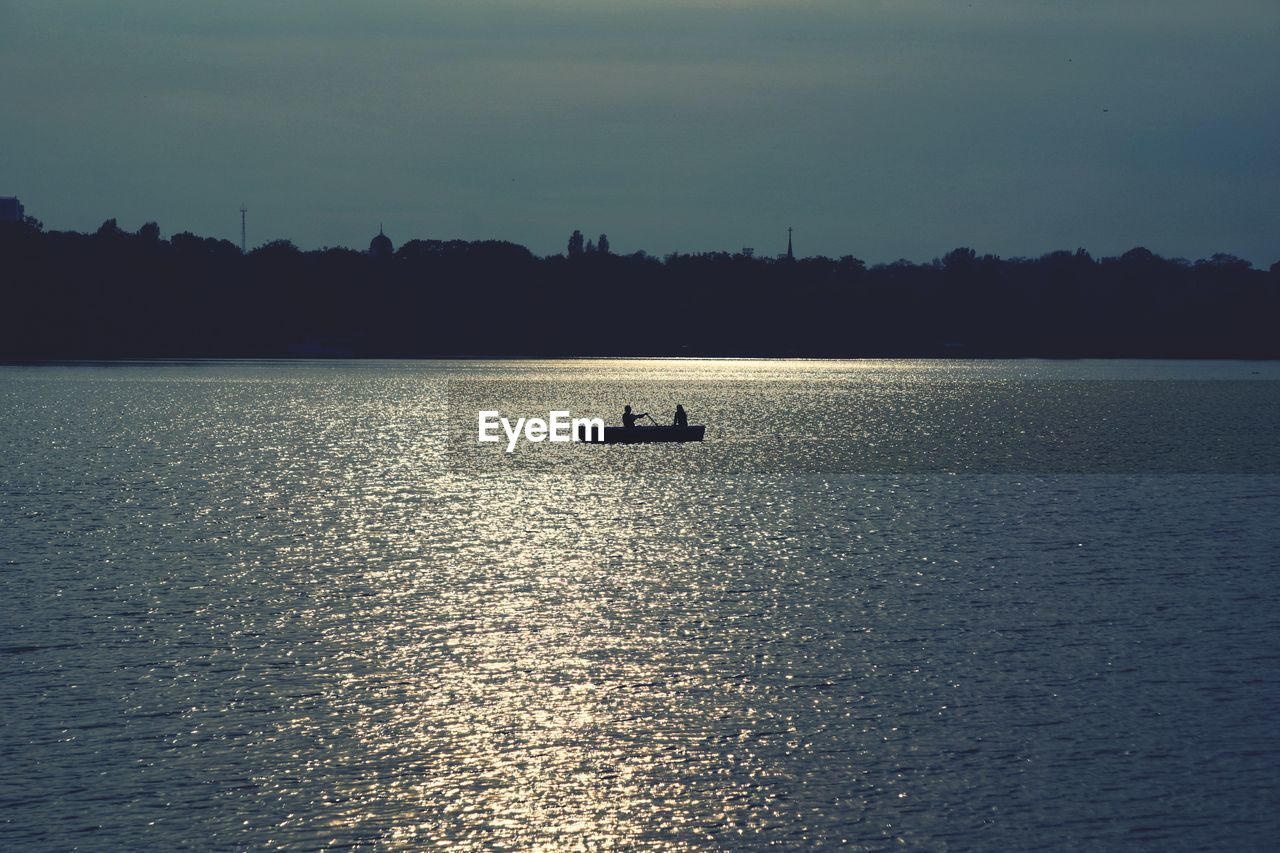 silhouette, waterfront, water, nature, transportation, tranquility, reflection, nautical vessel, tranquil scene, outdoors, beauty in nature, scenics, sunset, sea, sky, real people, day, sailing