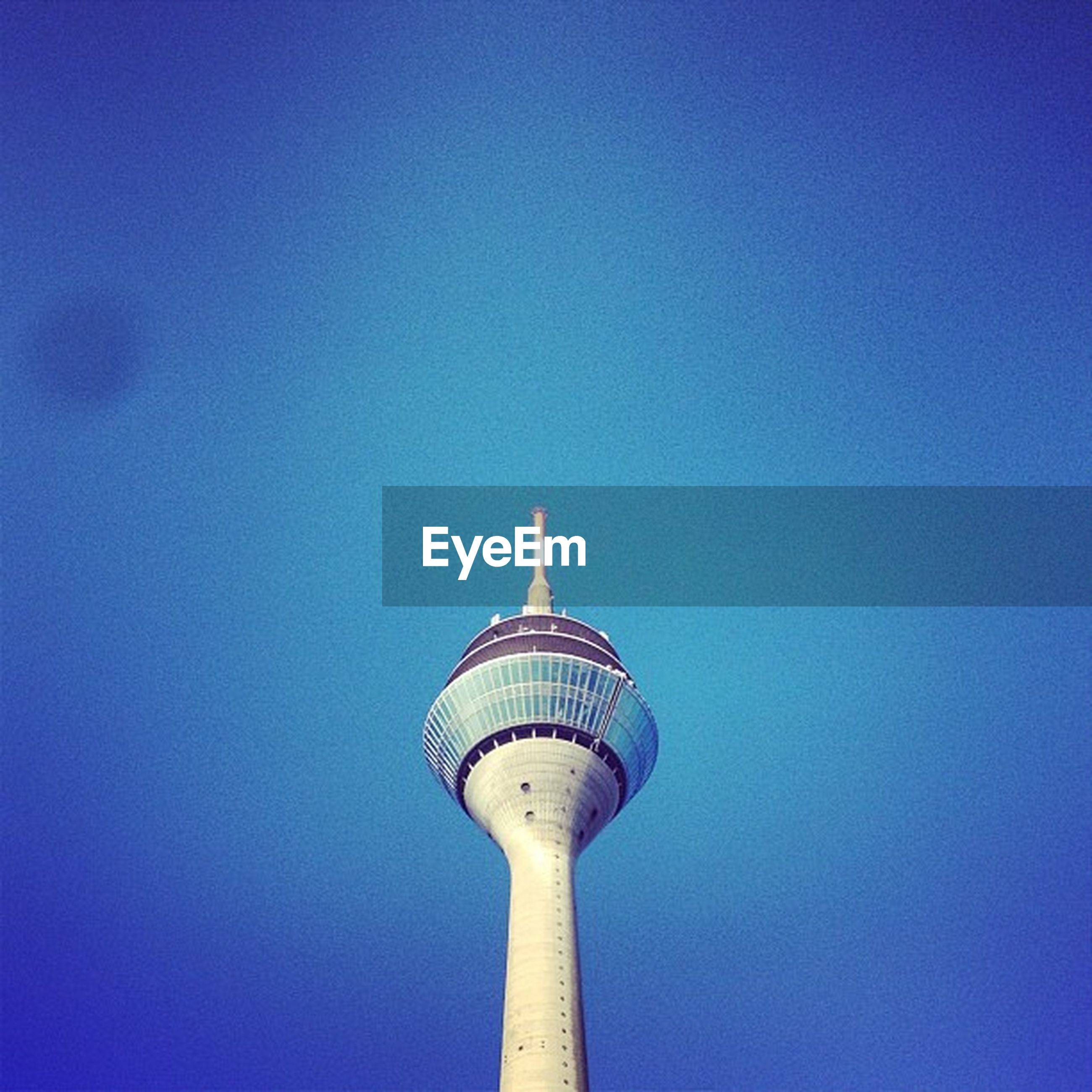 low angle view, tower, architecture, built structure, communications tower, clear sky, blue, tall - high, communication, building exterior, copy space, international landmark, famous place, capital cities, spire, travel destinations, tourism, fernsehturm, travel, television tower