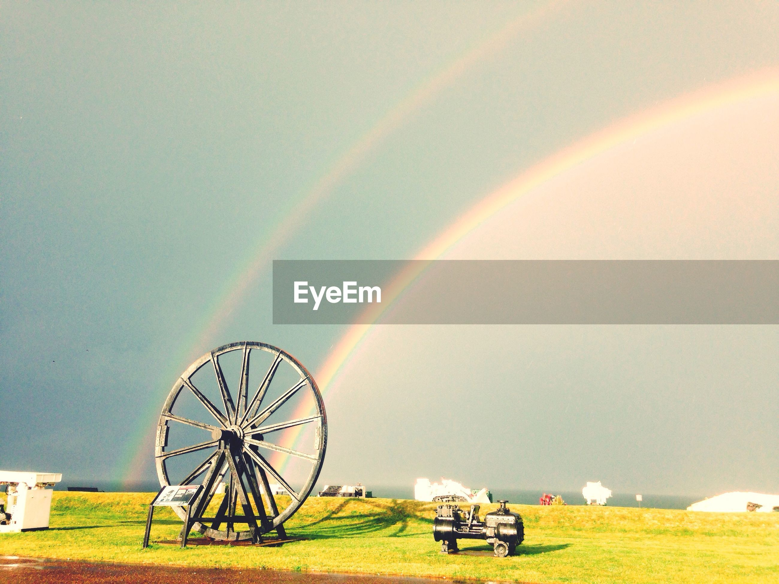rainbow, grass, multi colored, landscape, transportation, rural scene, cloud, ferris wheel, clear sky, grassland, day, nature, arch, tranquil scene, countryside, beauty in nature, scenics, outdoors, sky, tranquility, colorful, green, agriculture, large, circle, solitude