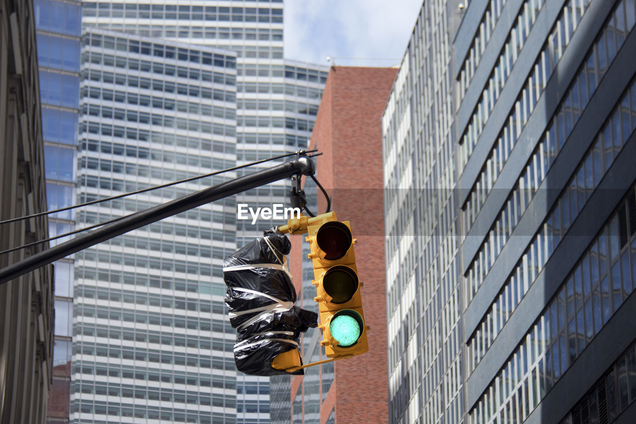Low Angle View Of Road Signal And Buildings Against Sky In City