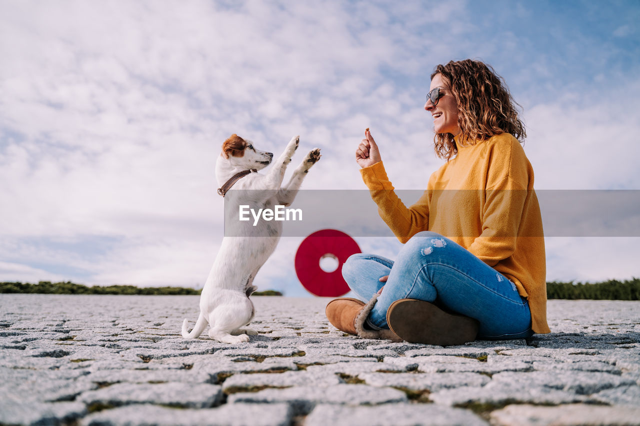 Side view of woman with dog sitting outdoors
