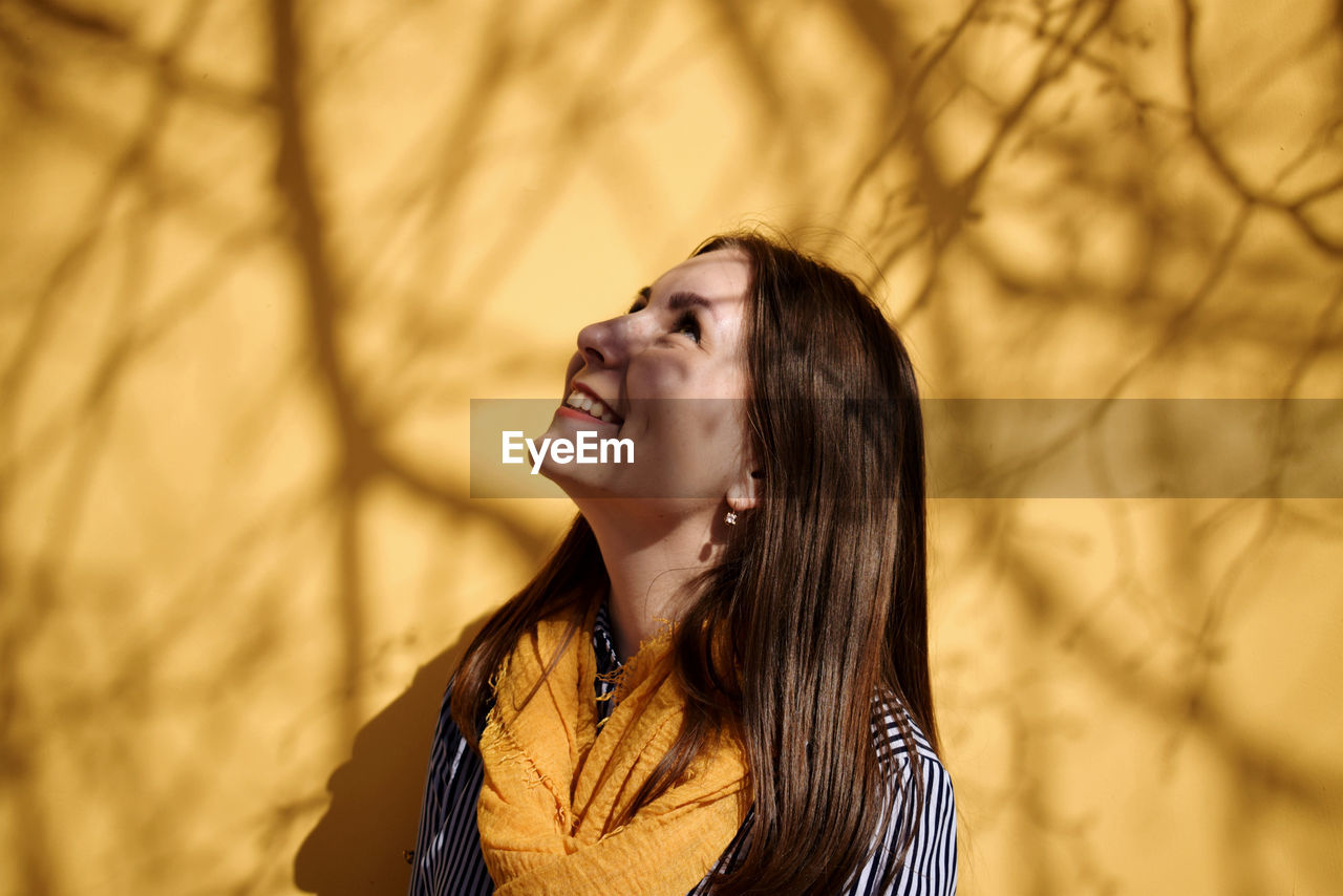 Smiling Young Woman Looking Up While Standing Against Yellow Wall