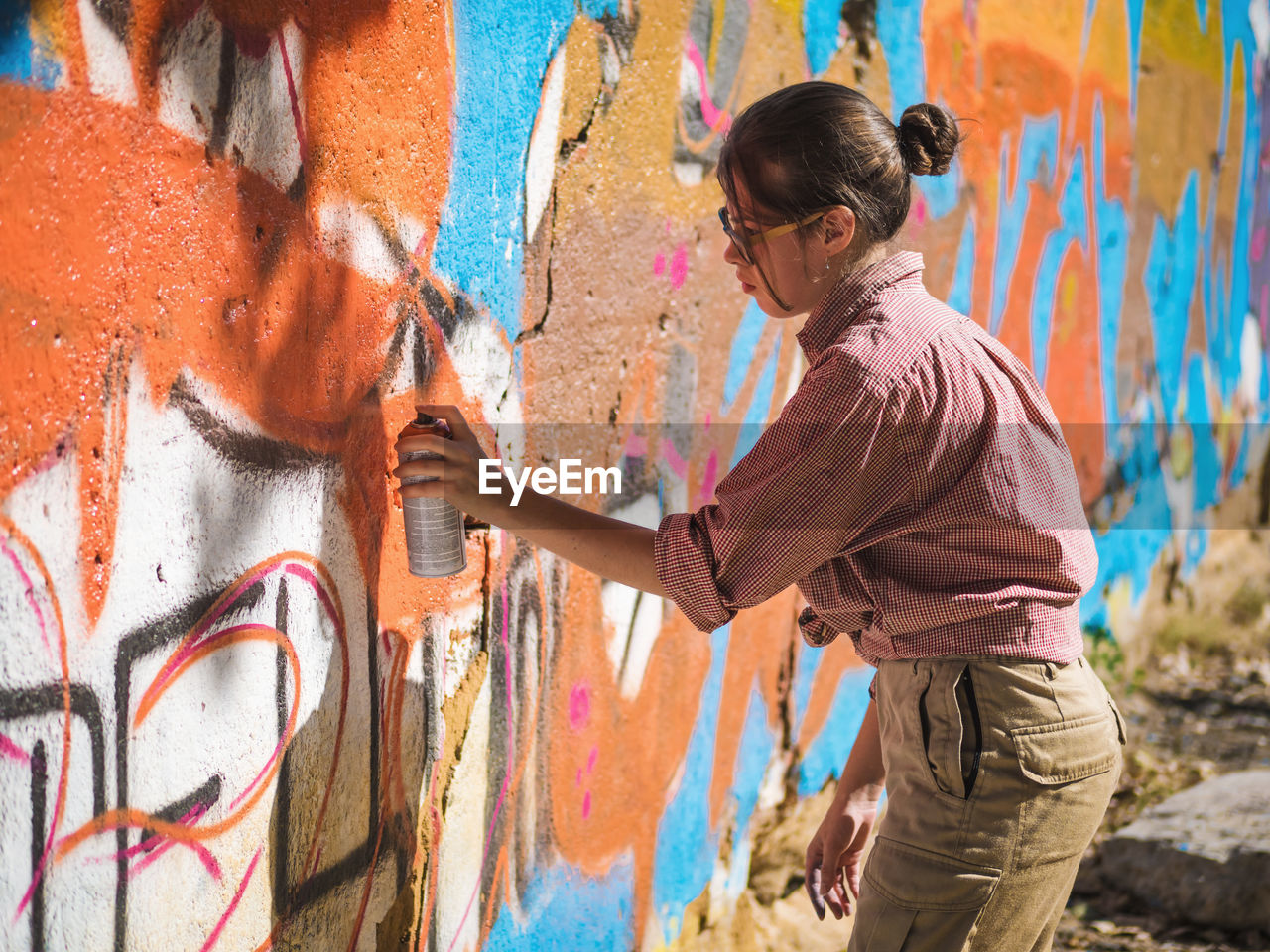 Side View Of Young Woman Spraying Graffiti On Wall