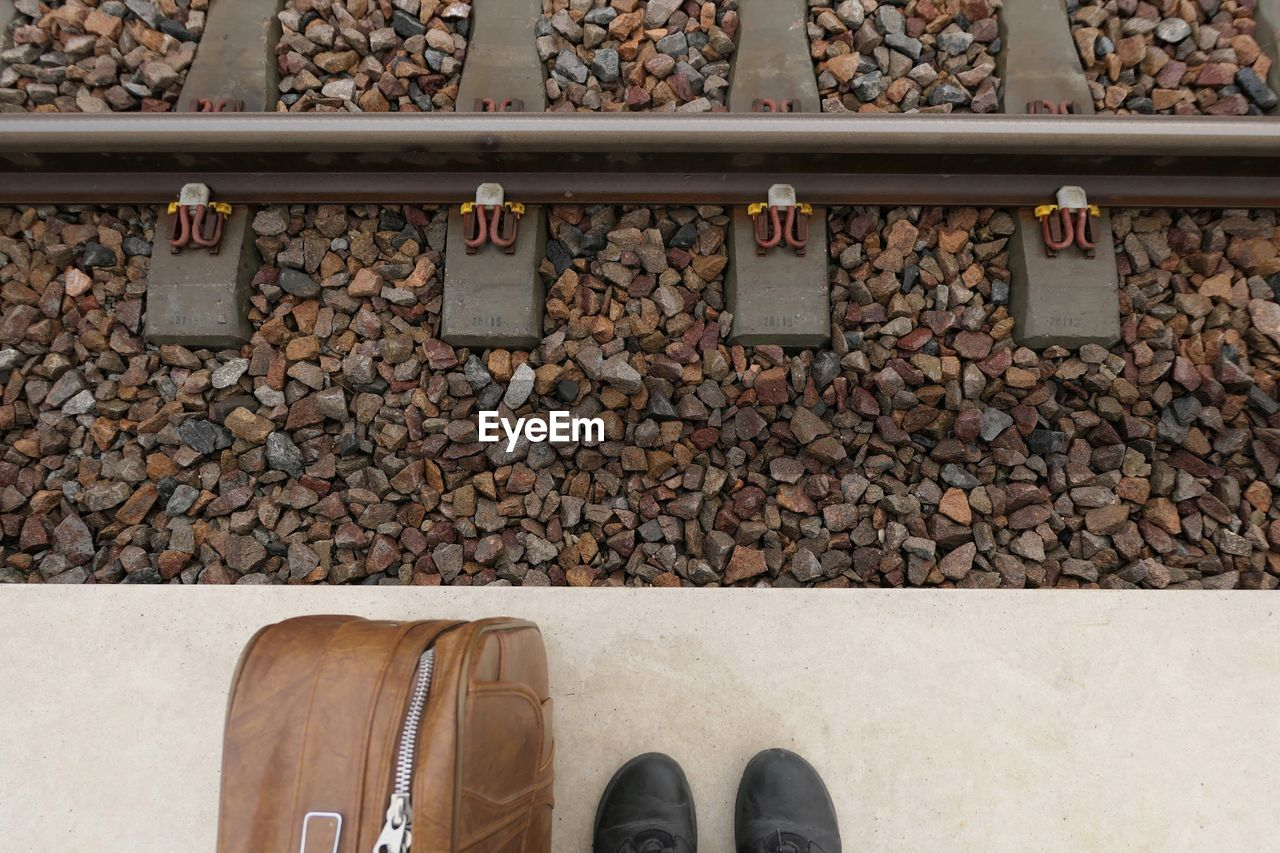 Low Section Of Person Standing With Luggage On Railroad Station Platform