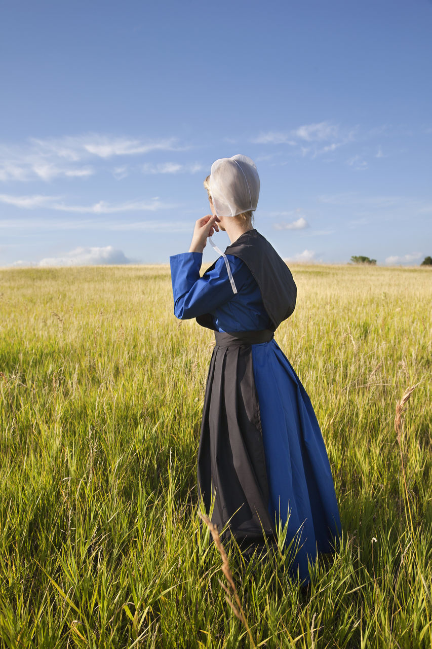 Rear View Of Woman Standing On Field Against Blue Sky