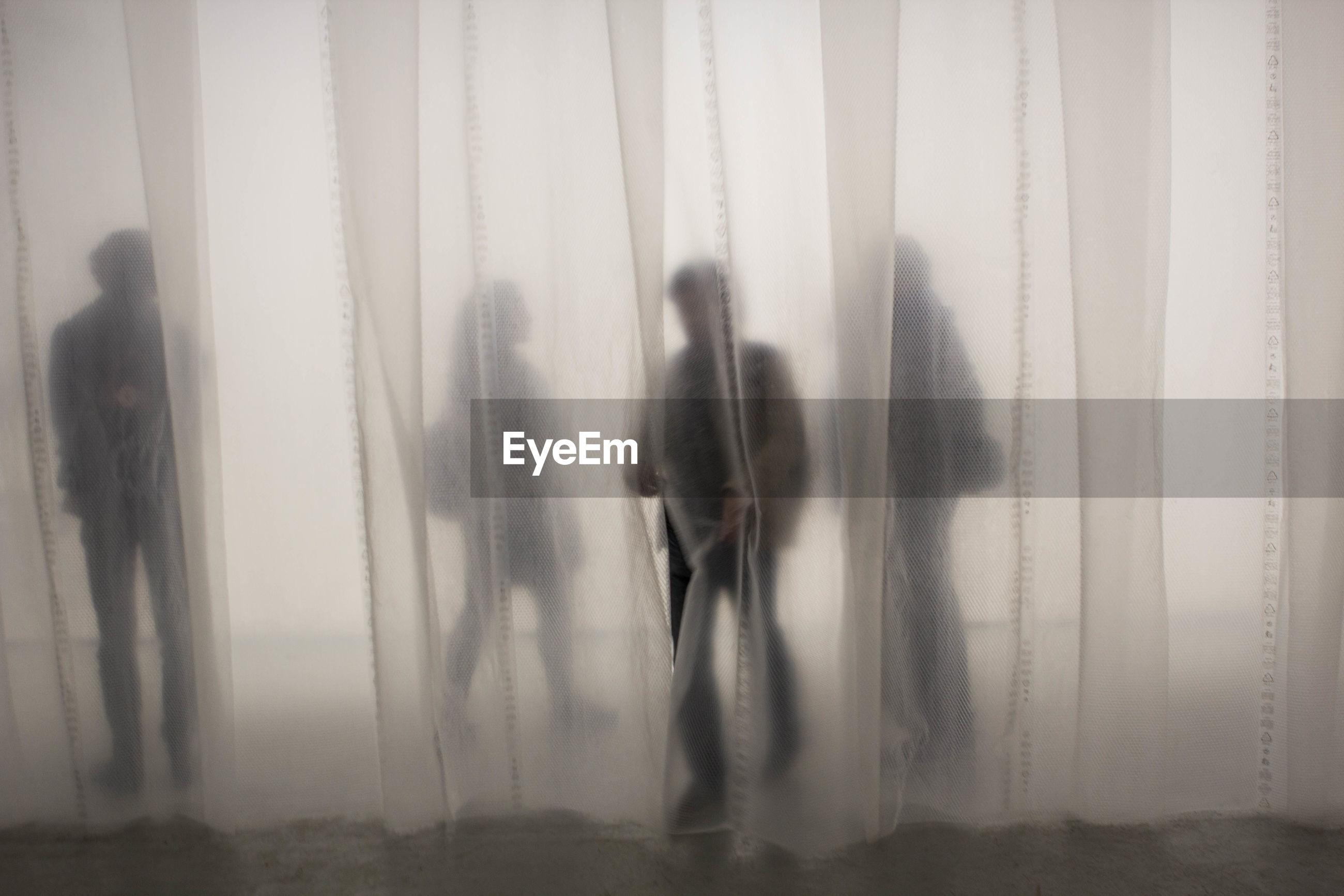 Shadow of people behind curtain