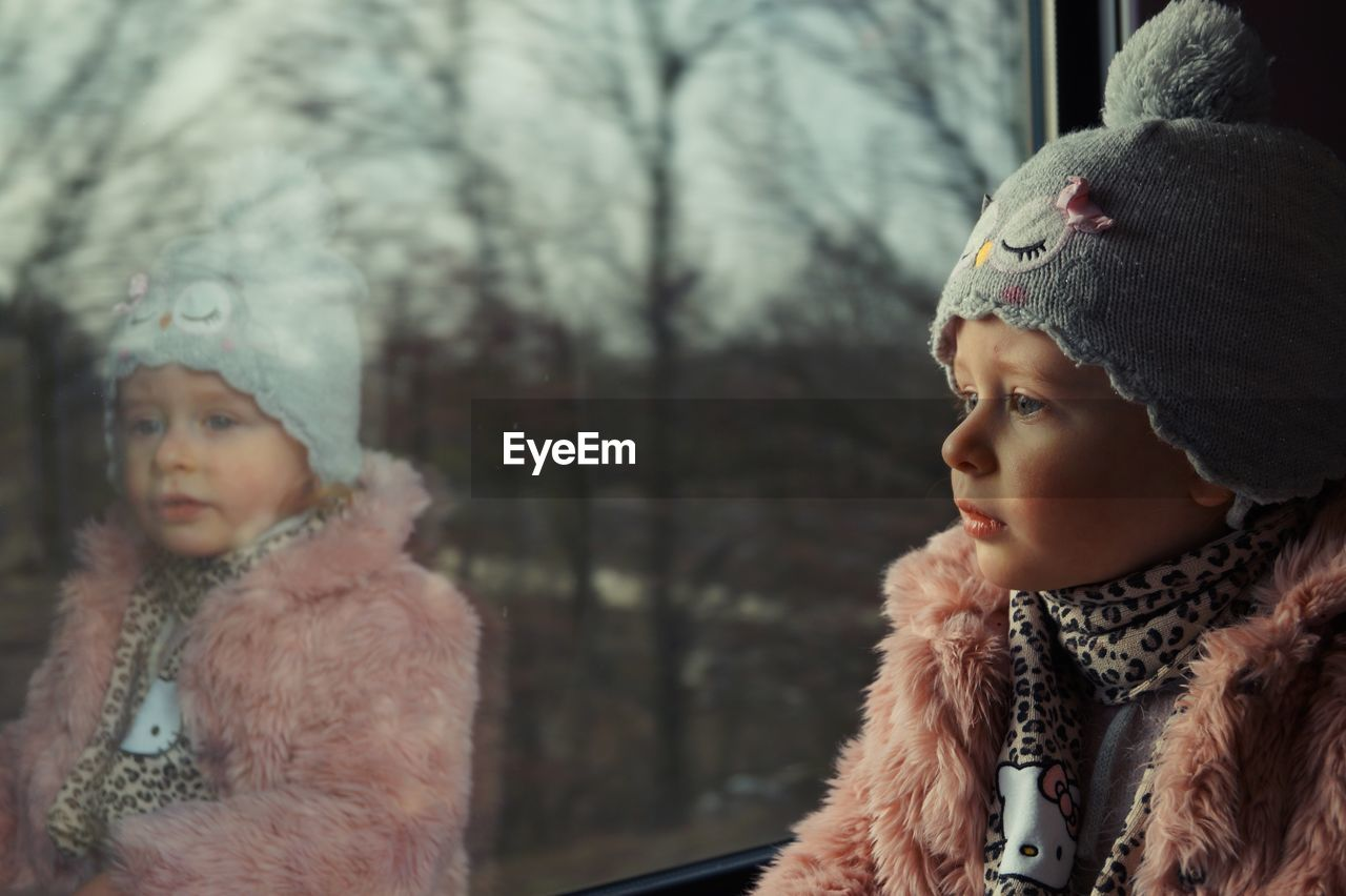 Cute girl looking through window while sitting at home during winter