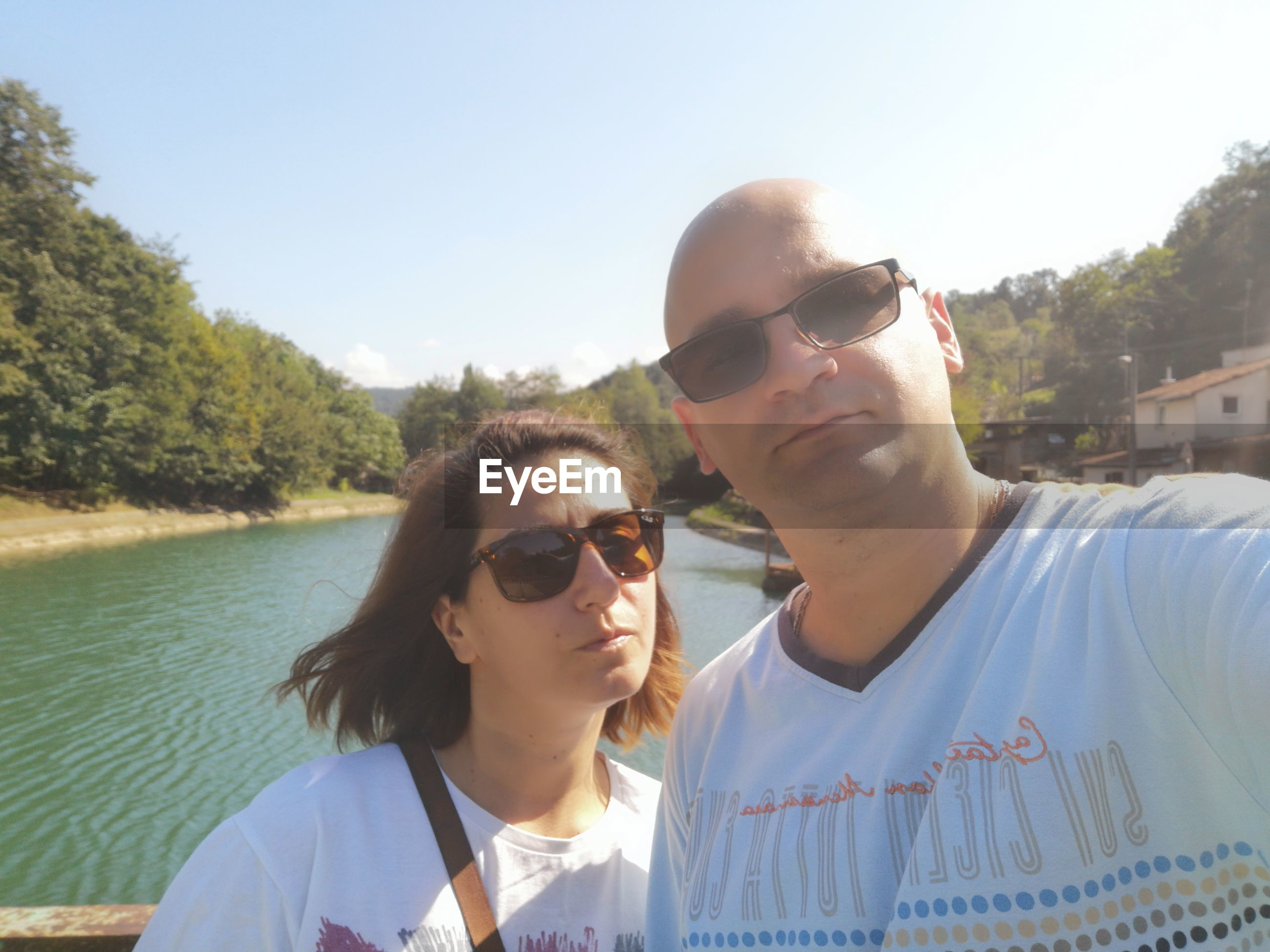 Portrait of couple in sunglasses against lake
