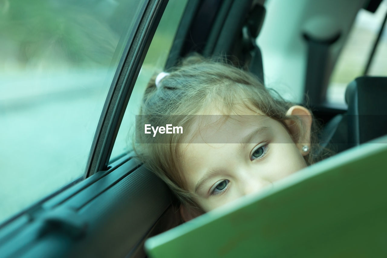 car, mode of transportation, childhood, motor vehicle, one person, portrait, transportation, real people, land vehicle, child, selective focus, headshot, car interior, vehicle interior, cute, travel, innocence, looking, road trip