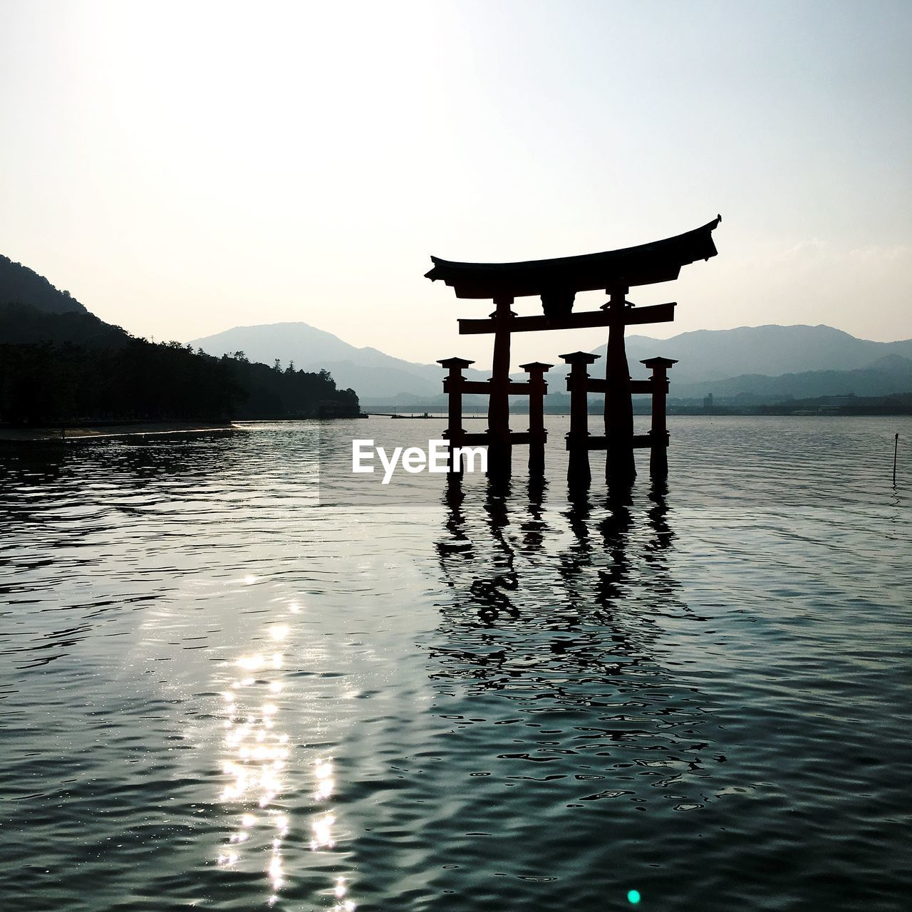 water, mountain, sky, religion, belief, tranquil scene, waterfront, tranquility, beauty in nature, nature, no people, spirituality, scenics - nature, silhouette, reflection, outdoors, lake, place of worship, non-urban scene, shrine