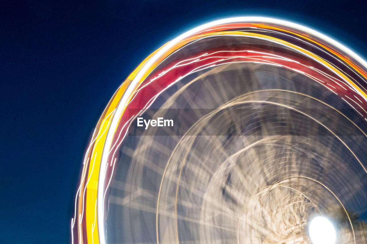 Blurred motion of illuminated ferris wheel at night