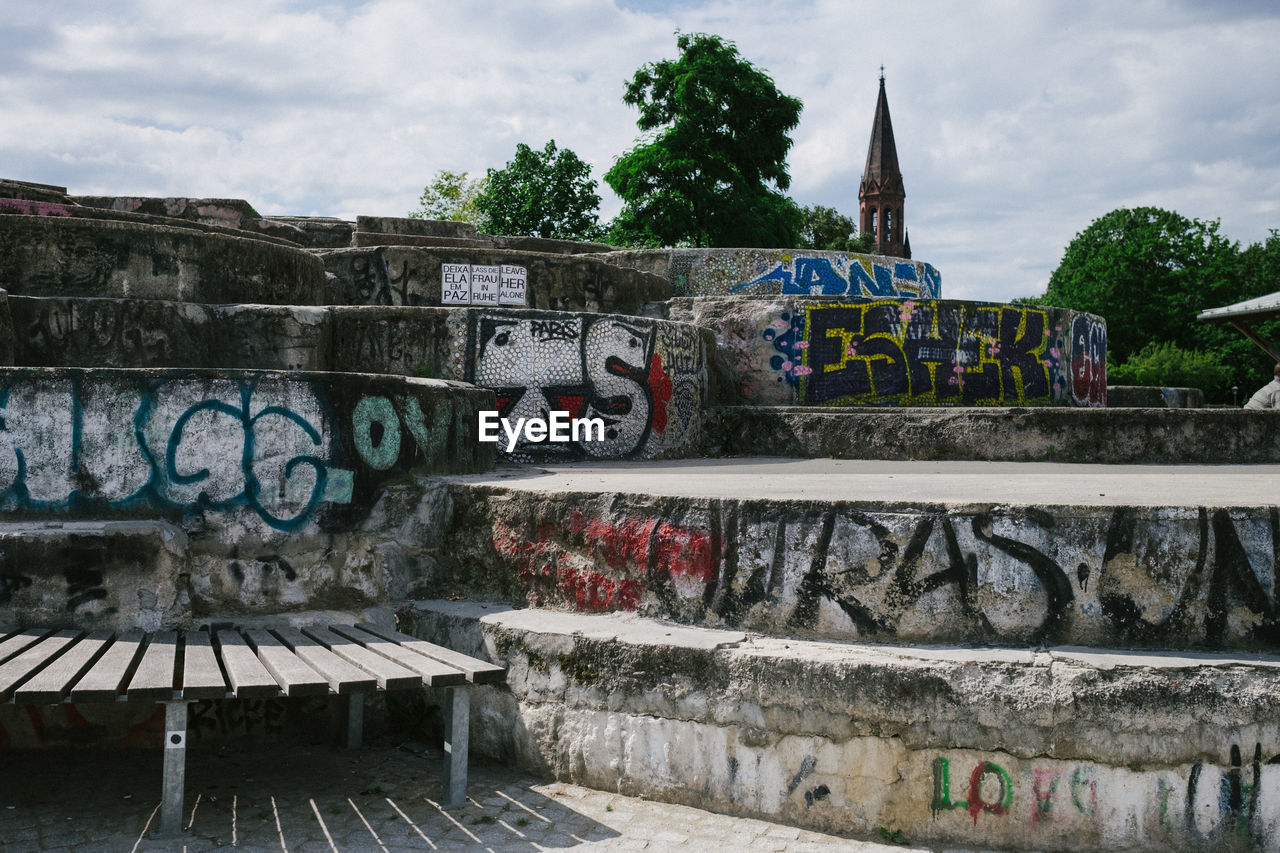 graffiti, text, creativity, built structure, art and craft, day, architecture, communication, cloud - sky, sky, building exterior, outdoors, street art, no people, water, city