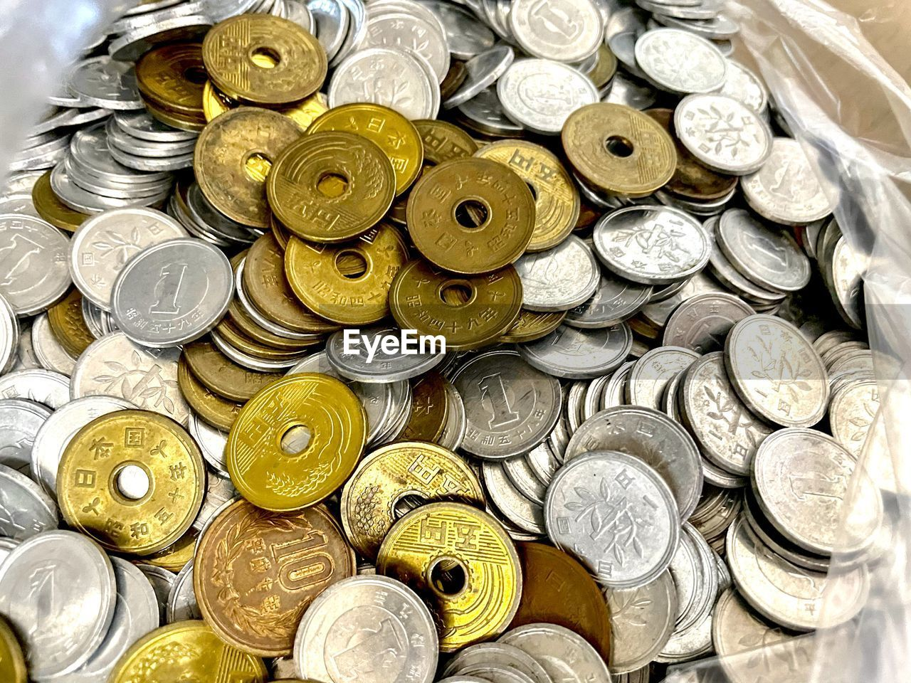 HIGH ANGLE VIEW OF COINS ON METAL GRATE