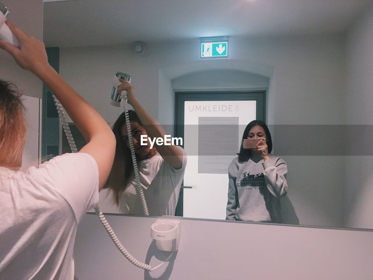 Young woman taking mirror selfie while friend drying hair in restroom