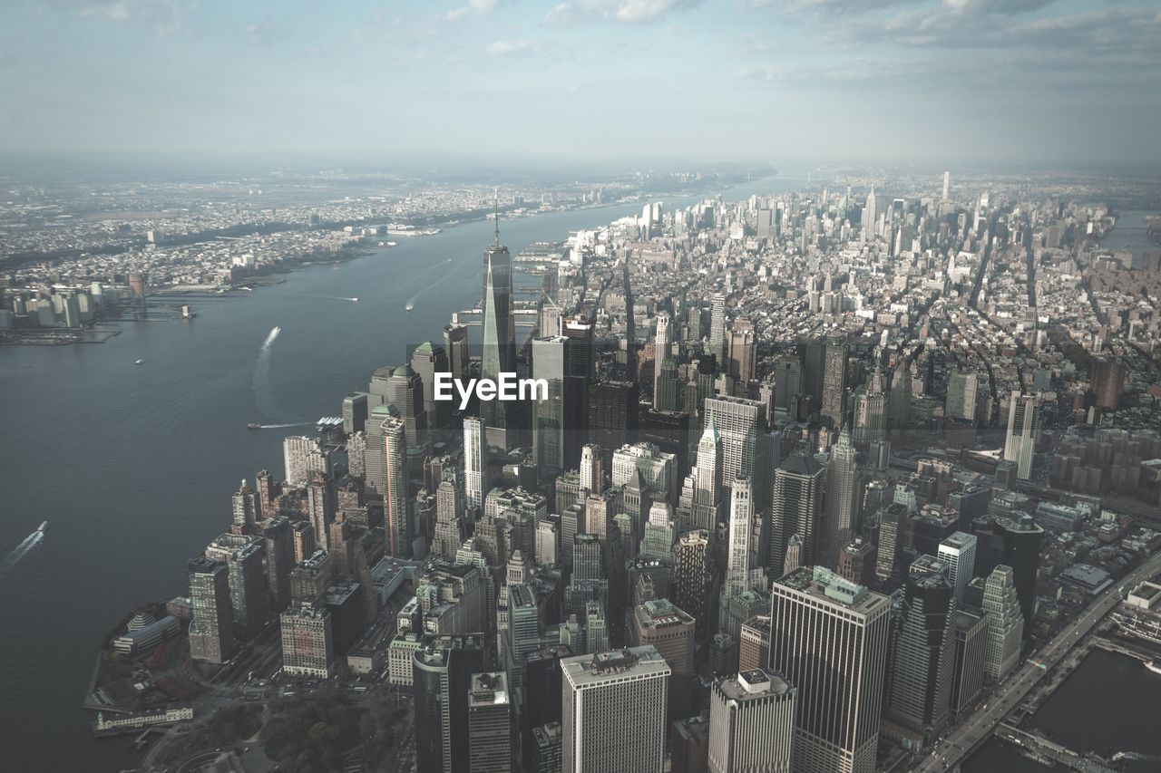 Aerial view of new york city by sea against sky