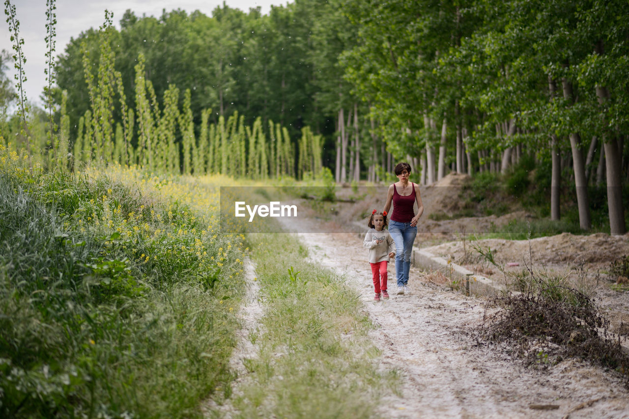 Mother And Daughter Walking In Forest