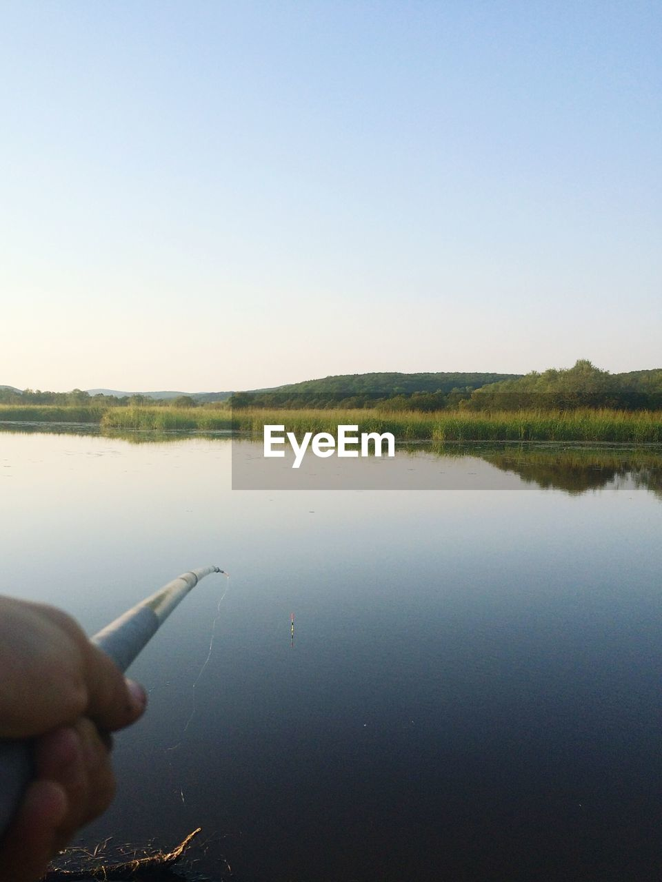 human hand, human finger, human body part, clear sky, one person, real people, reflection, copy space, water, lake, holding, outdoors, sky, day, nature, close-up, beauty in nature, people