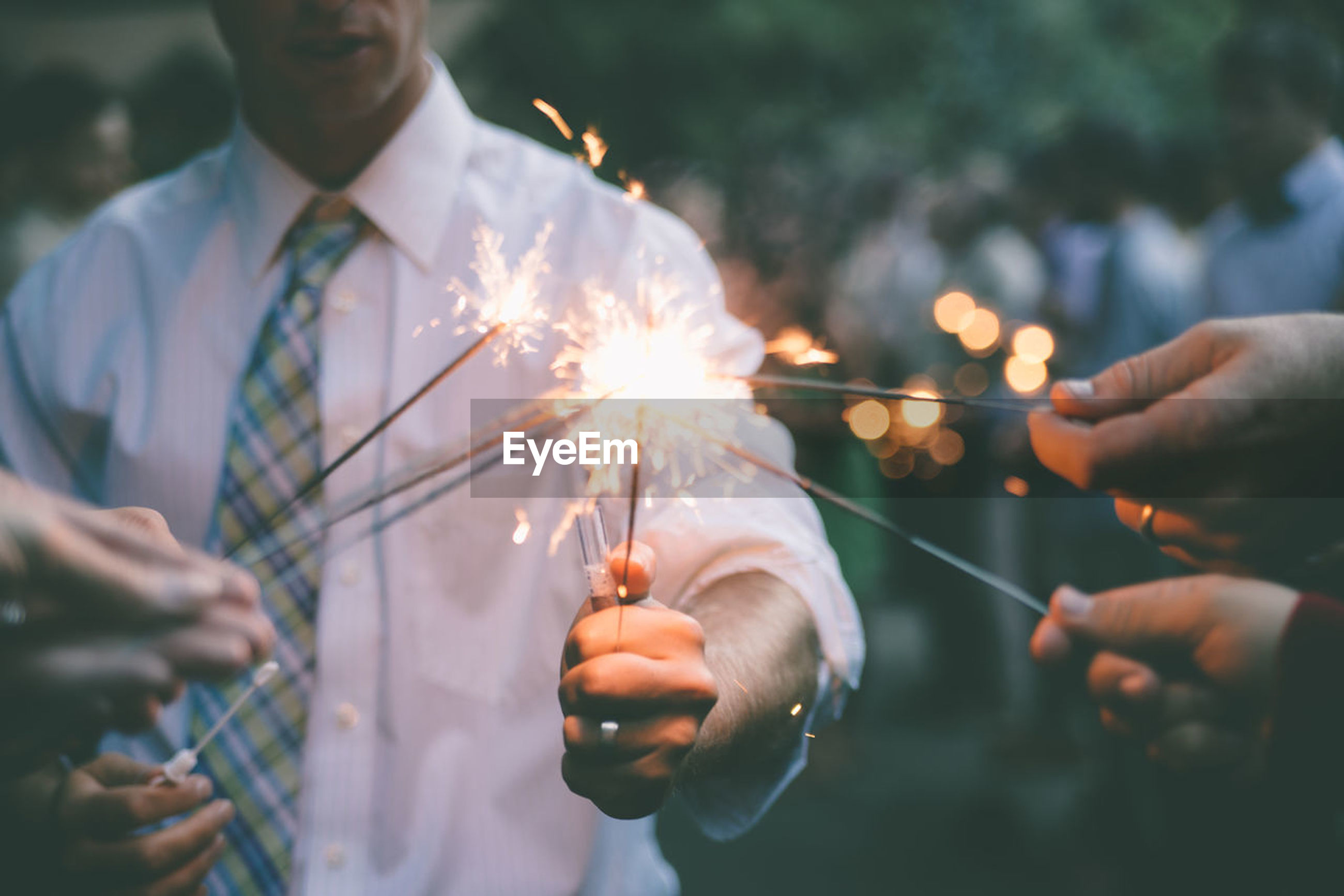 burning, holding, real people, event, celebration, sparkler, human hand, illuminated, glowing, focus on foreground, men, hand, people, fire, lifestyles, fire - natural phenomenon, motion, leisure activity, nature, sparks, firework, outdoors, firework - man made object