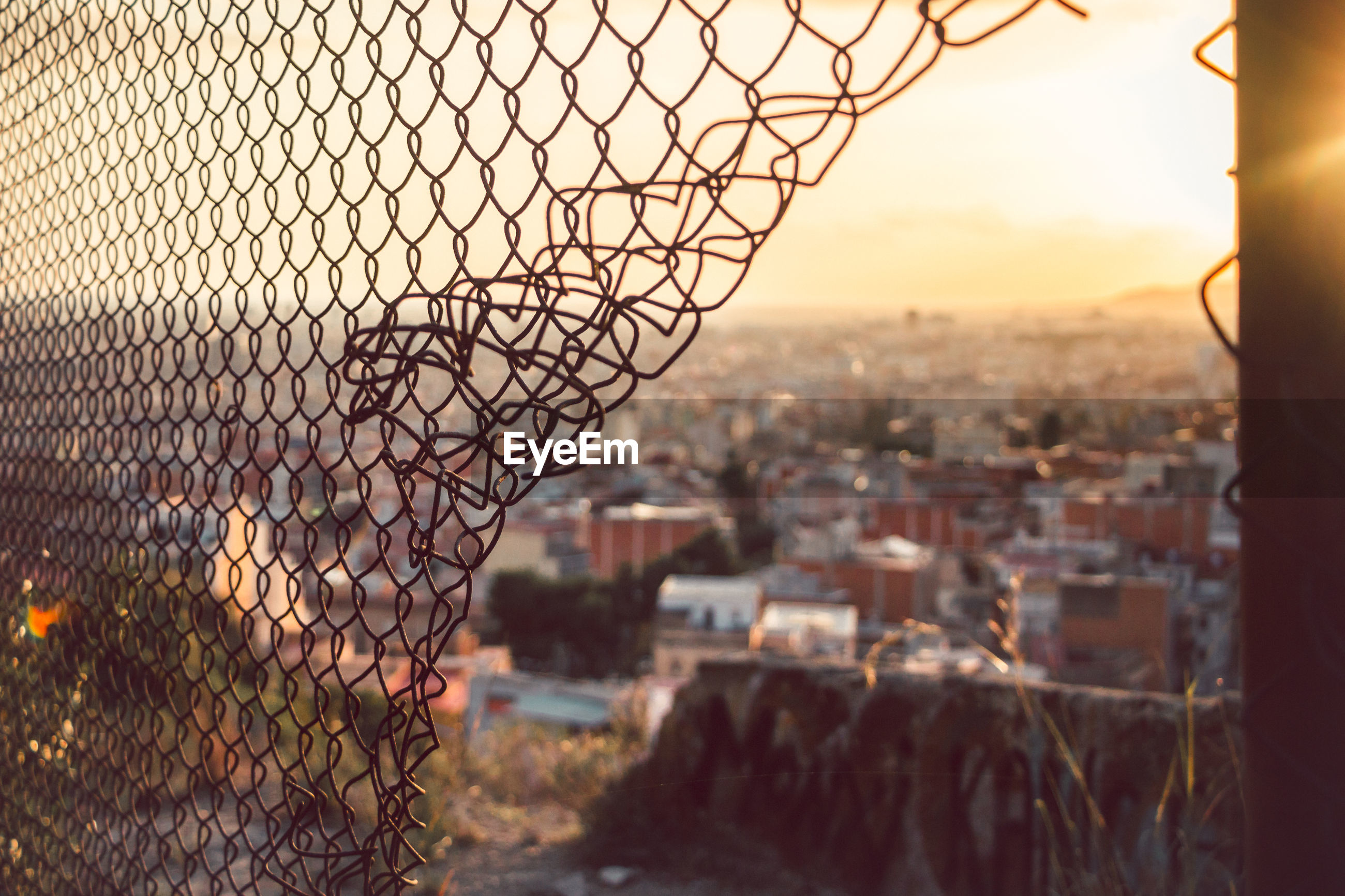 Town seen from broken chainlink fence at morning