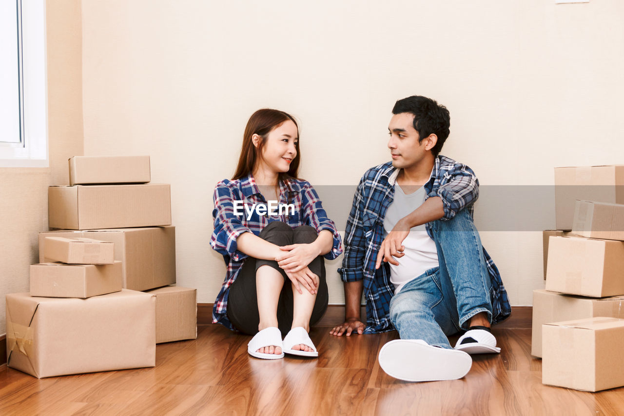 box, cardboard box, two people, cardboard, young adult, young women, couple - relationship, togetherness, indoors, women, moving house, heterosexual couple, flooring, beginnings, lifestyles, full length, young men, adult, relocation, young couple, change, box - container, packing, unpacking, wood, home improvement