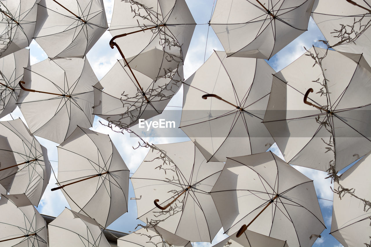 full frame, backgrounds, no people, low angle view, pattern, hanging, day, creativity, shape, umbrella, decoration, design, art and craft, architecture, close-up, built structure, white color, outdoors, paper, ceiling, directly below