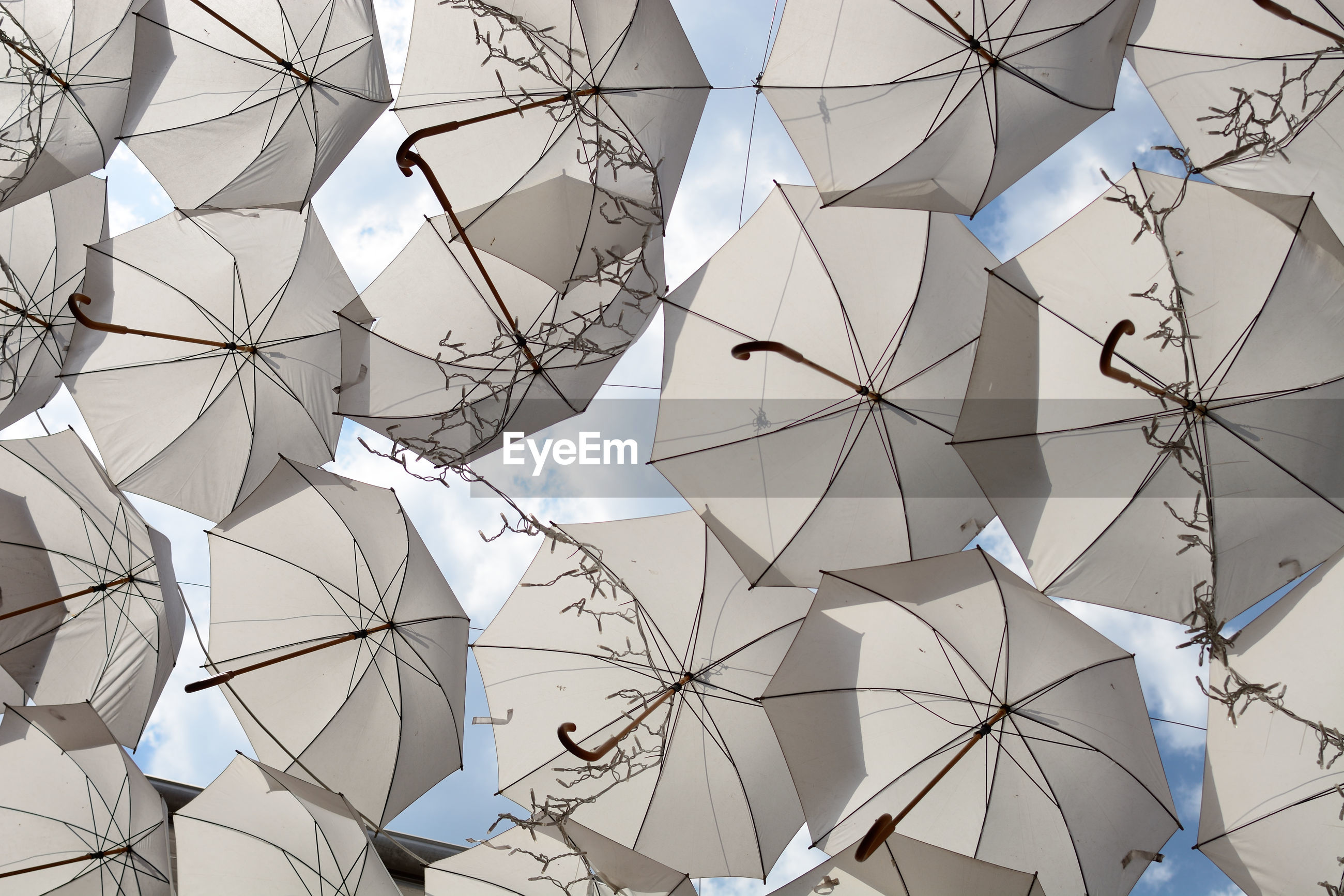 LOW ANGLE VIEW OF UMBRELLAS HANGING AGAINST CEILING