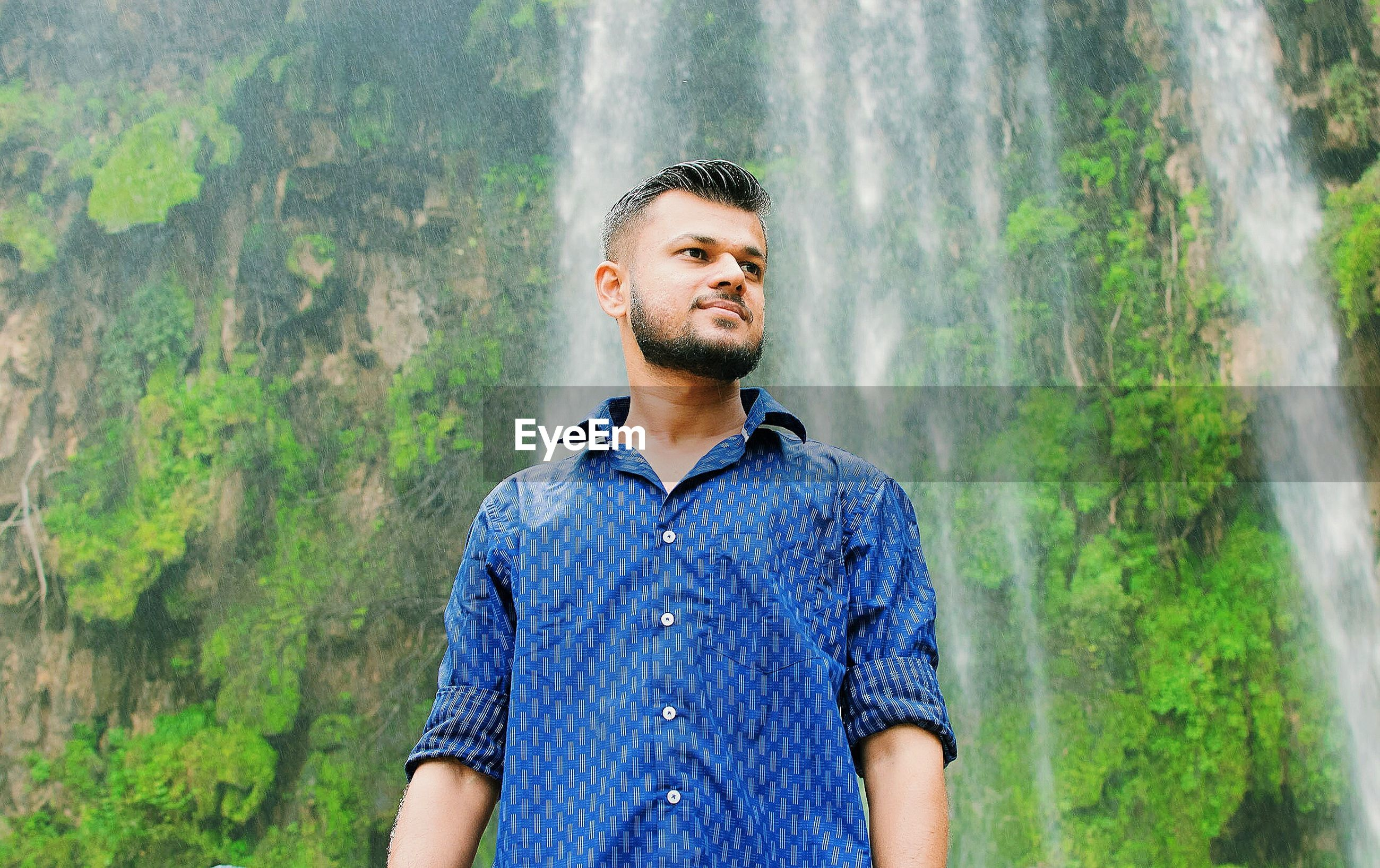 Young man standing against waterfall at forest
