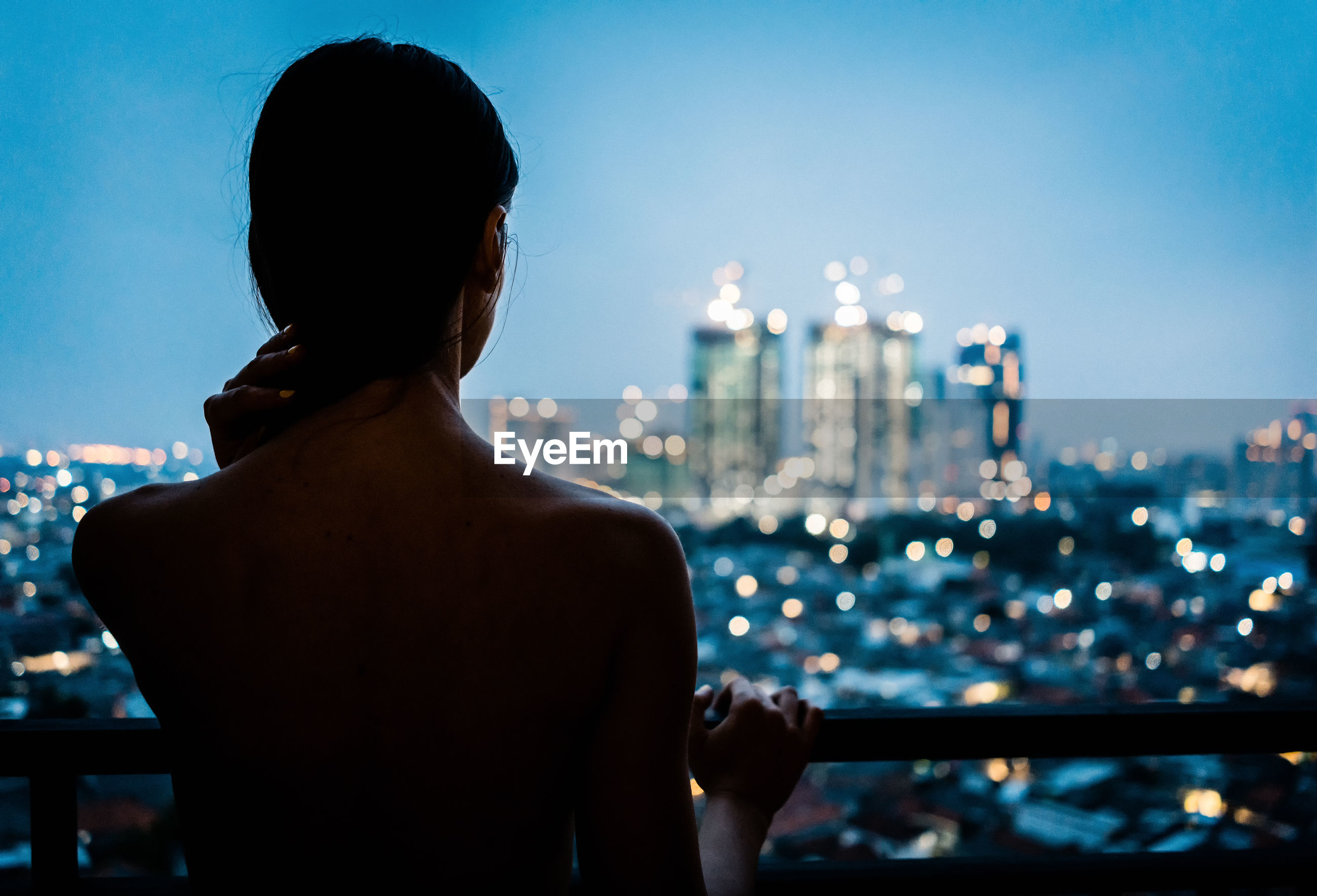 Rear view of shirtless woman looking at cityscape against sky