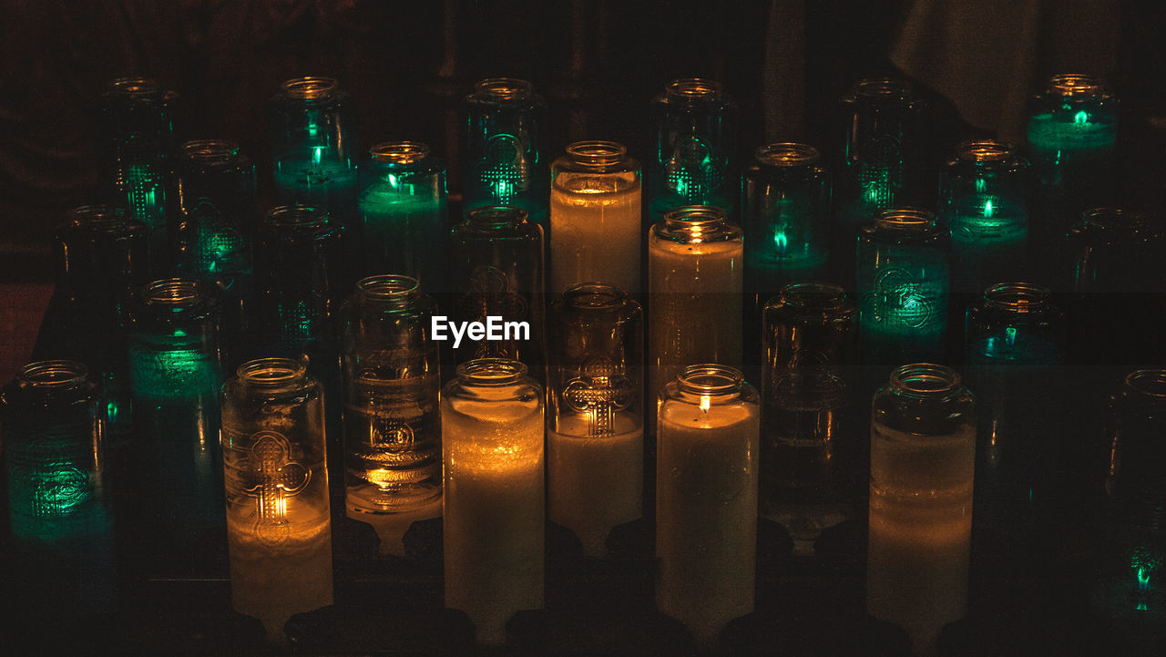 Close-up of illuminated candles in glass jars