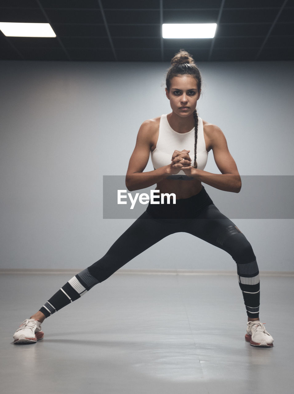 one person, full length, indoors, front view, exercising, portrait, looking at camera, lifestyles, young adult, sport, healthy lifestyle, young women, sports clothing, determination, confidence, practicing, flexibility, clothing, beautiful woman