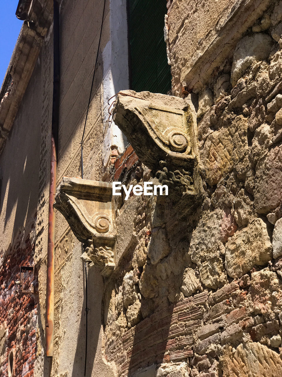 architecture, built structure, low angle view, building, building exterior, solid, day, no people, wall - building feature, the past, history, art and craft, nature, religion, craft, sunlight, old, representation, wall, belief, outdoors, stone wall, ruined