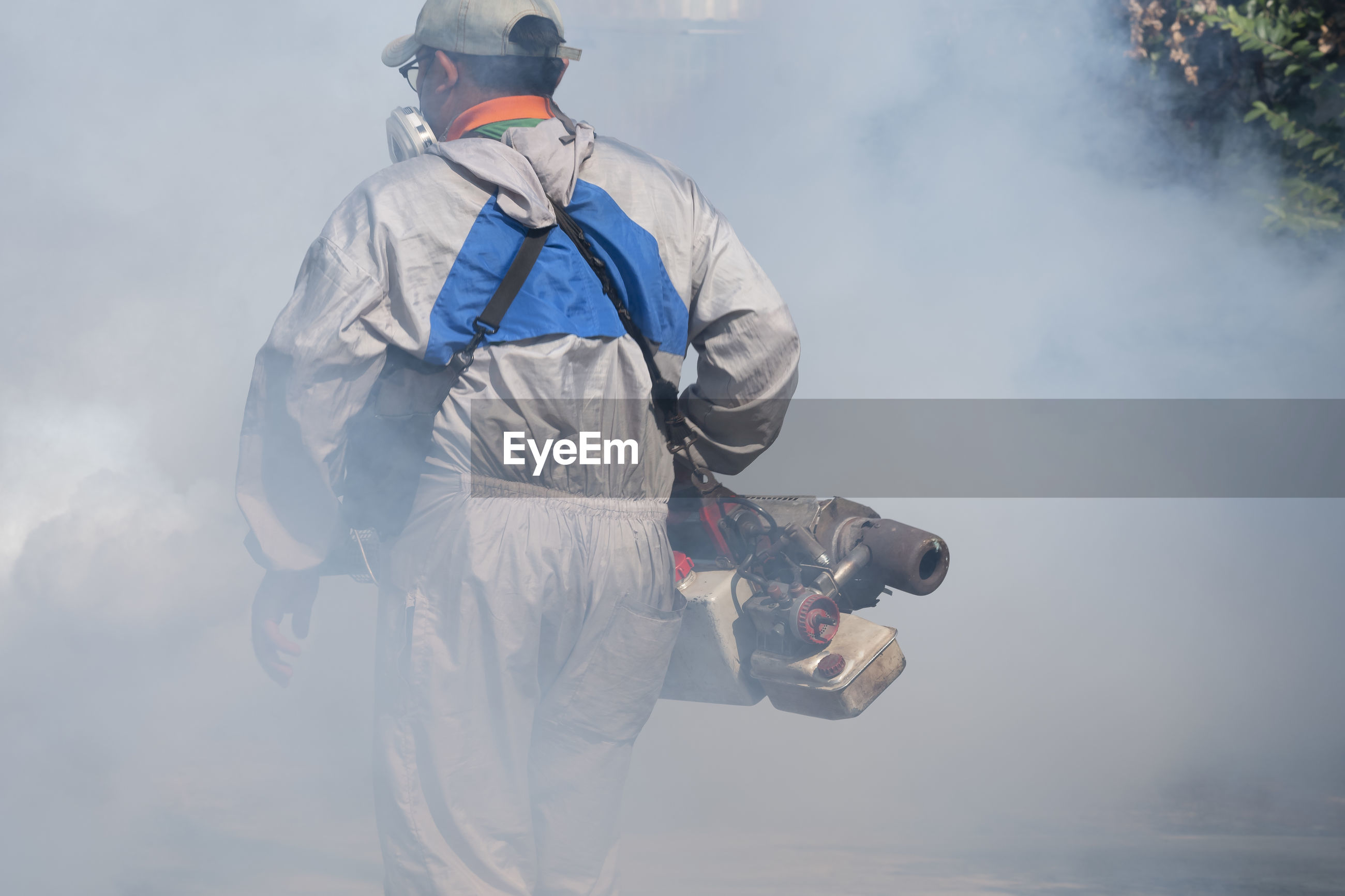 Rear view of man spraying insecticide