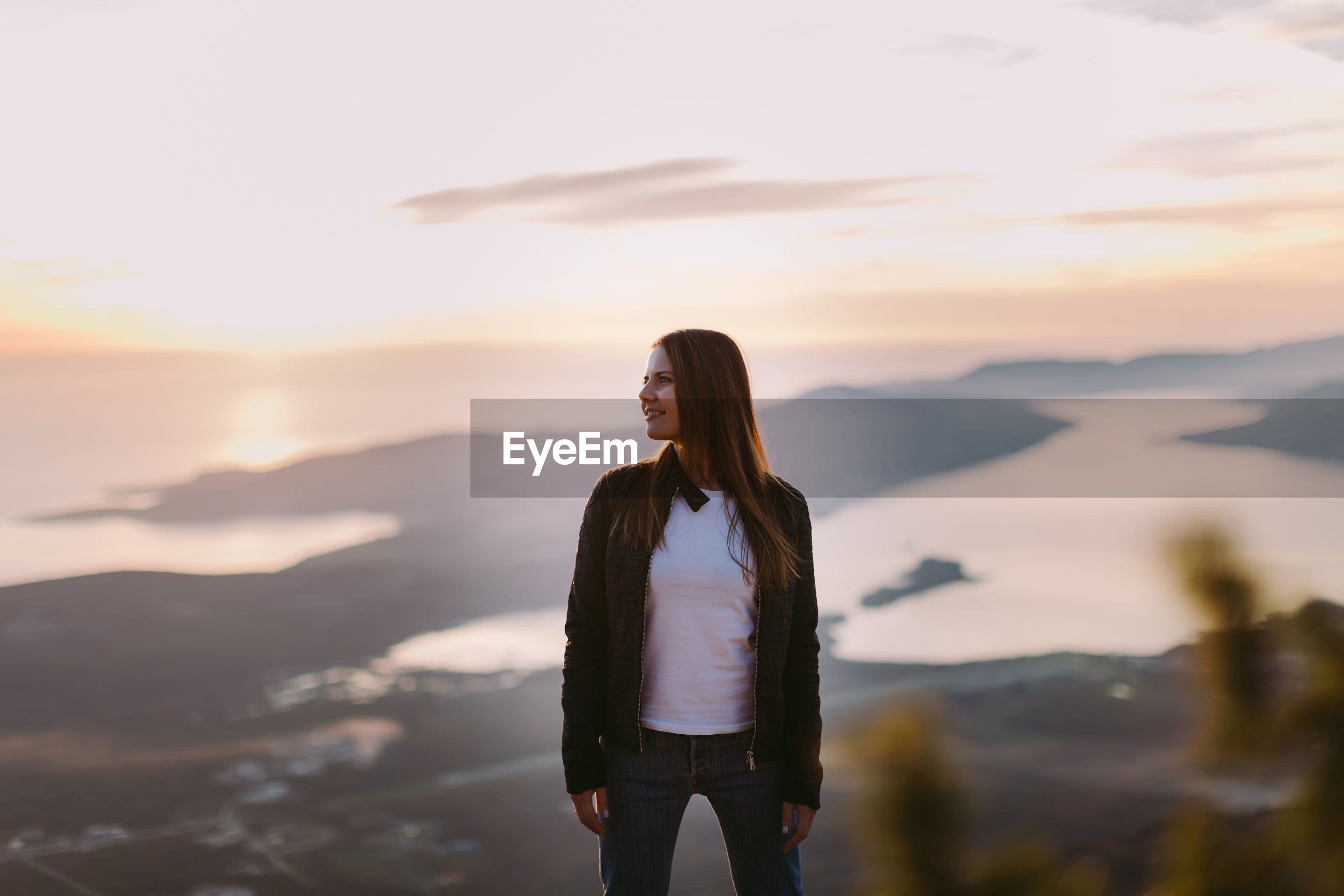 Woman looking away while standing against sky during sunset