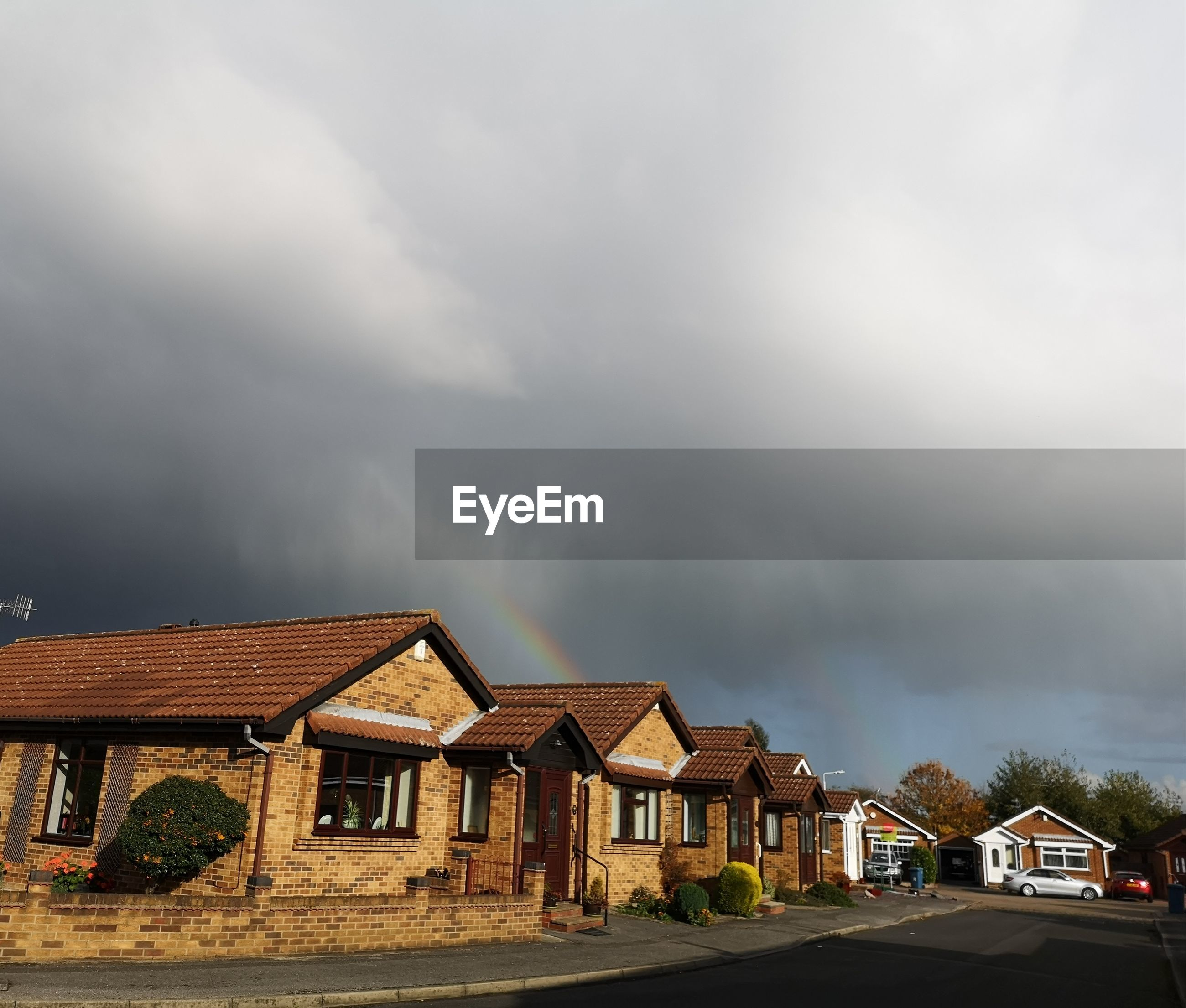 HOUSES BY ROAD AGAINST STORM CLOUDS