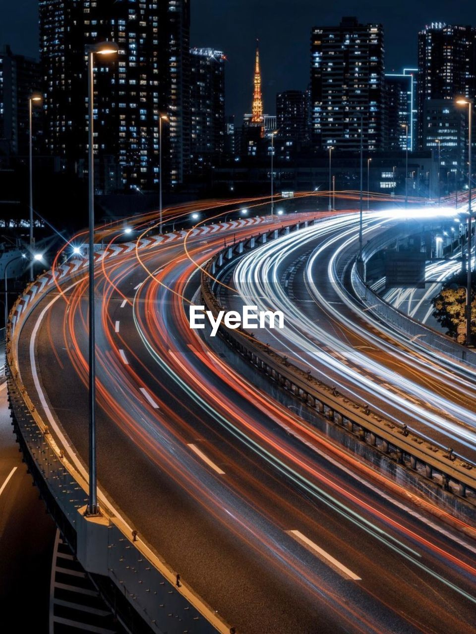 High angle view of light trails on road amidst buildings at night